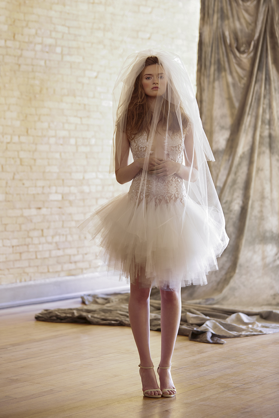 retouched bride standing in studio wearing short tutu wedding dress and veil