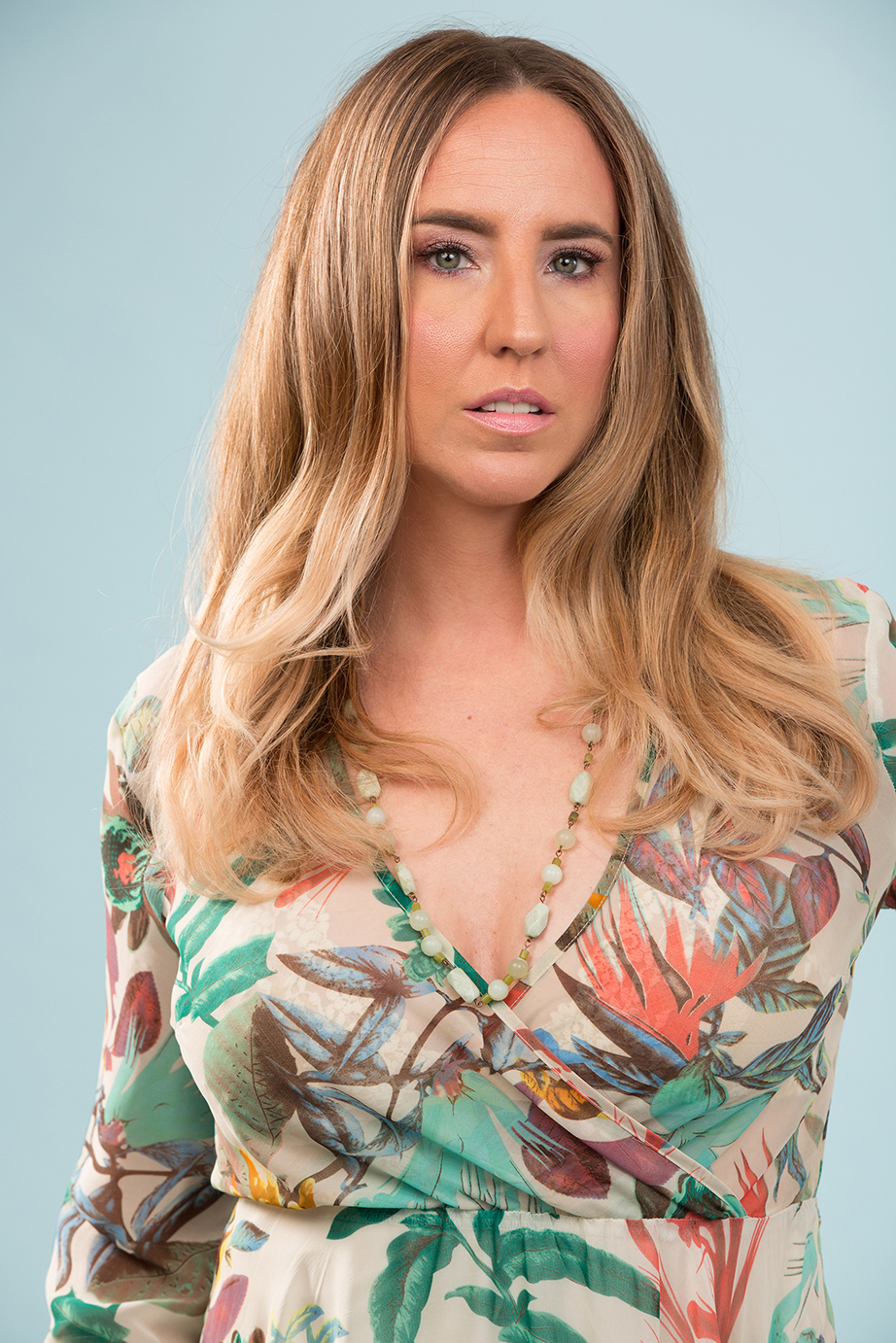 blonde woman in tropical floral wrap dress