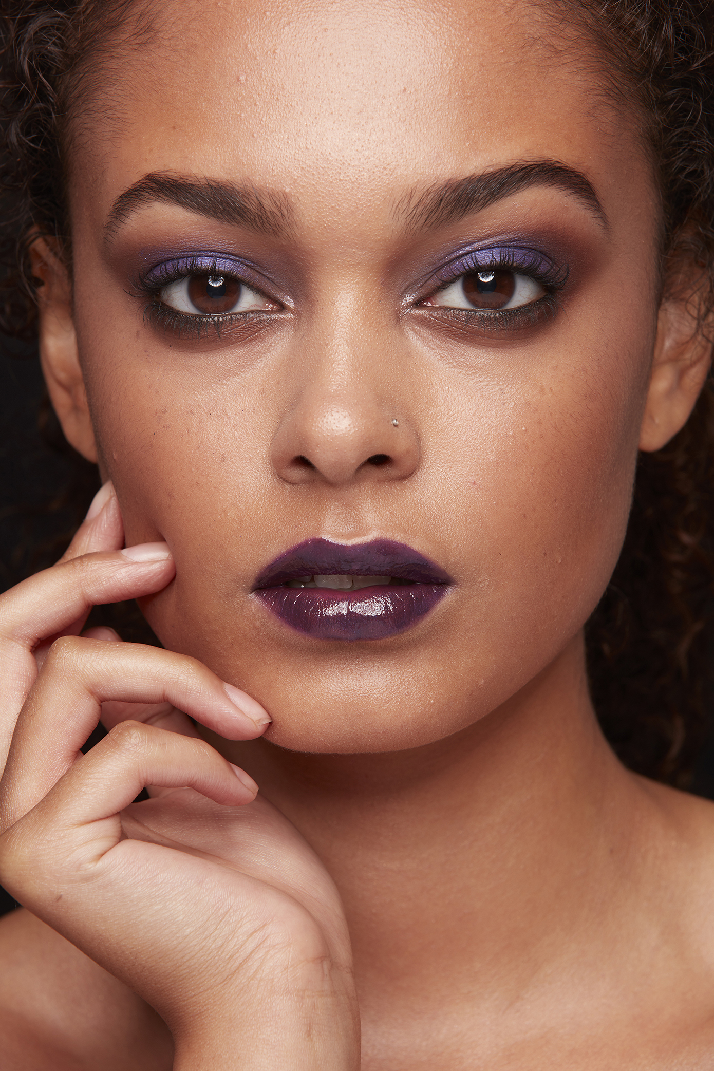 closeup of woman with purple amethyst eye shadow and purple lipstick, hand on face