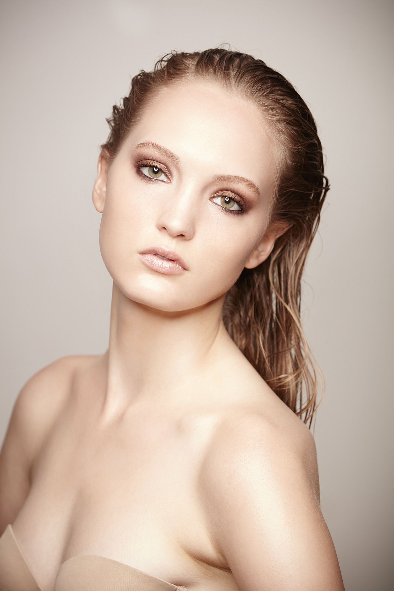 retouched woman in strapless bra with wet hair and neutral makeup