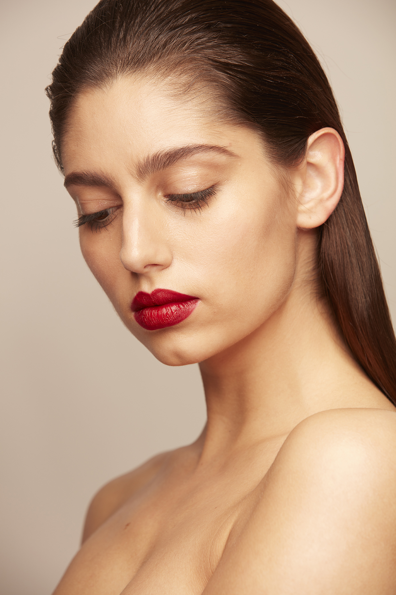 woman with swept back hair and red lipstick
