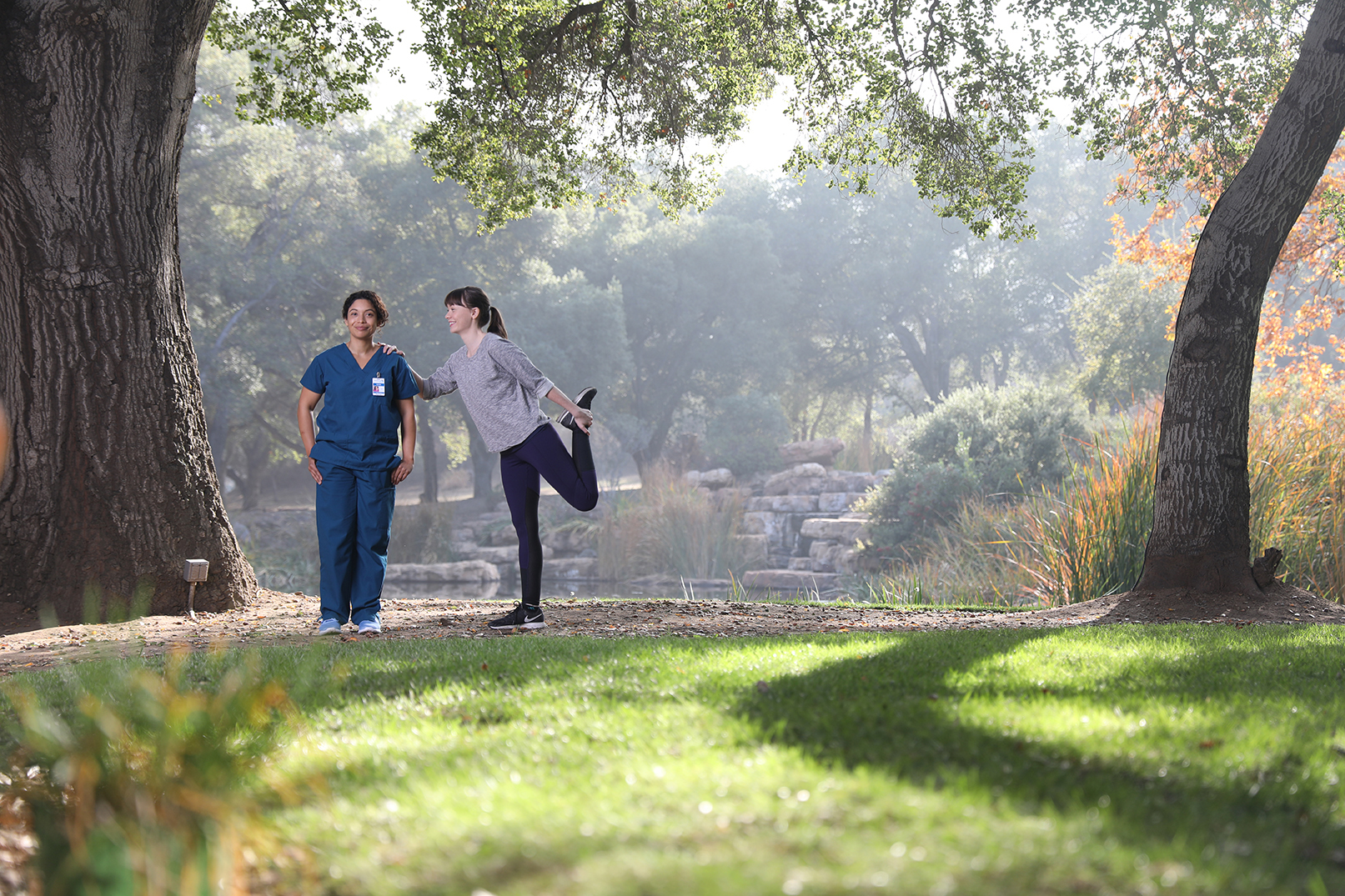 female jogger stretching in sunny park and leaning on nurse wearing scrubs