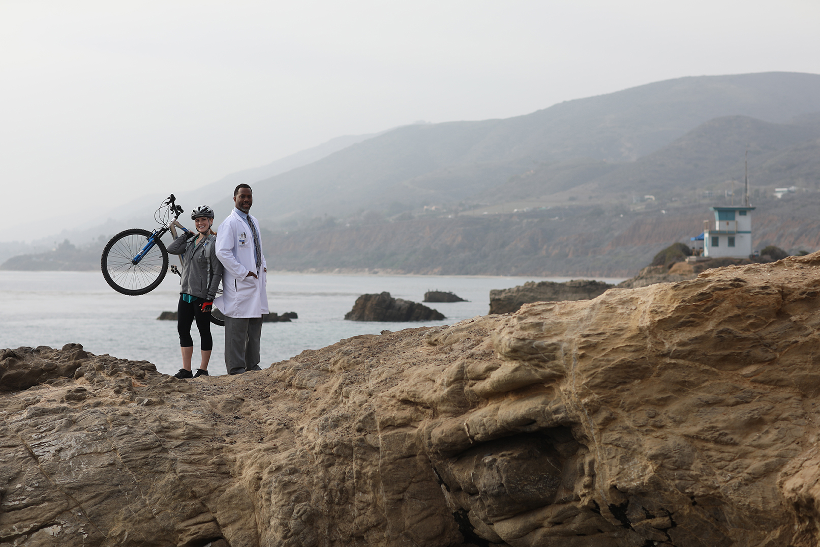 male doctor in white lab coat standing on rocky cliffside next to female mountain biker