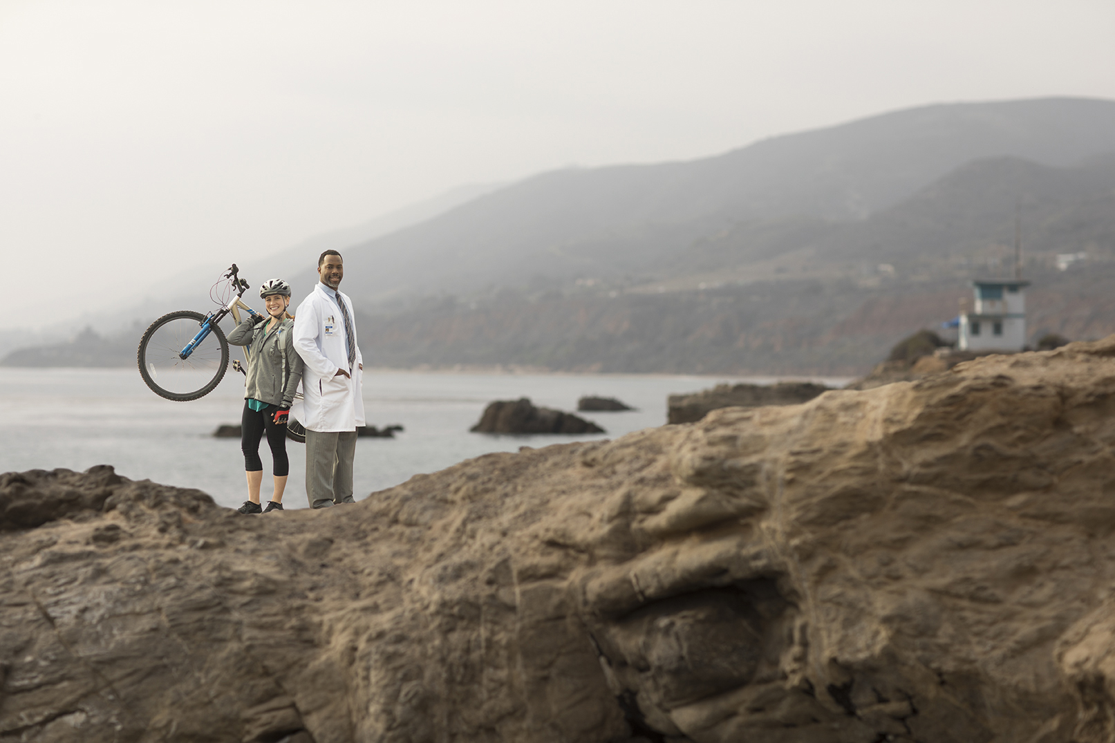 retouched male doctor in white lab coat standing on rocky cliffside next to female mountain biker