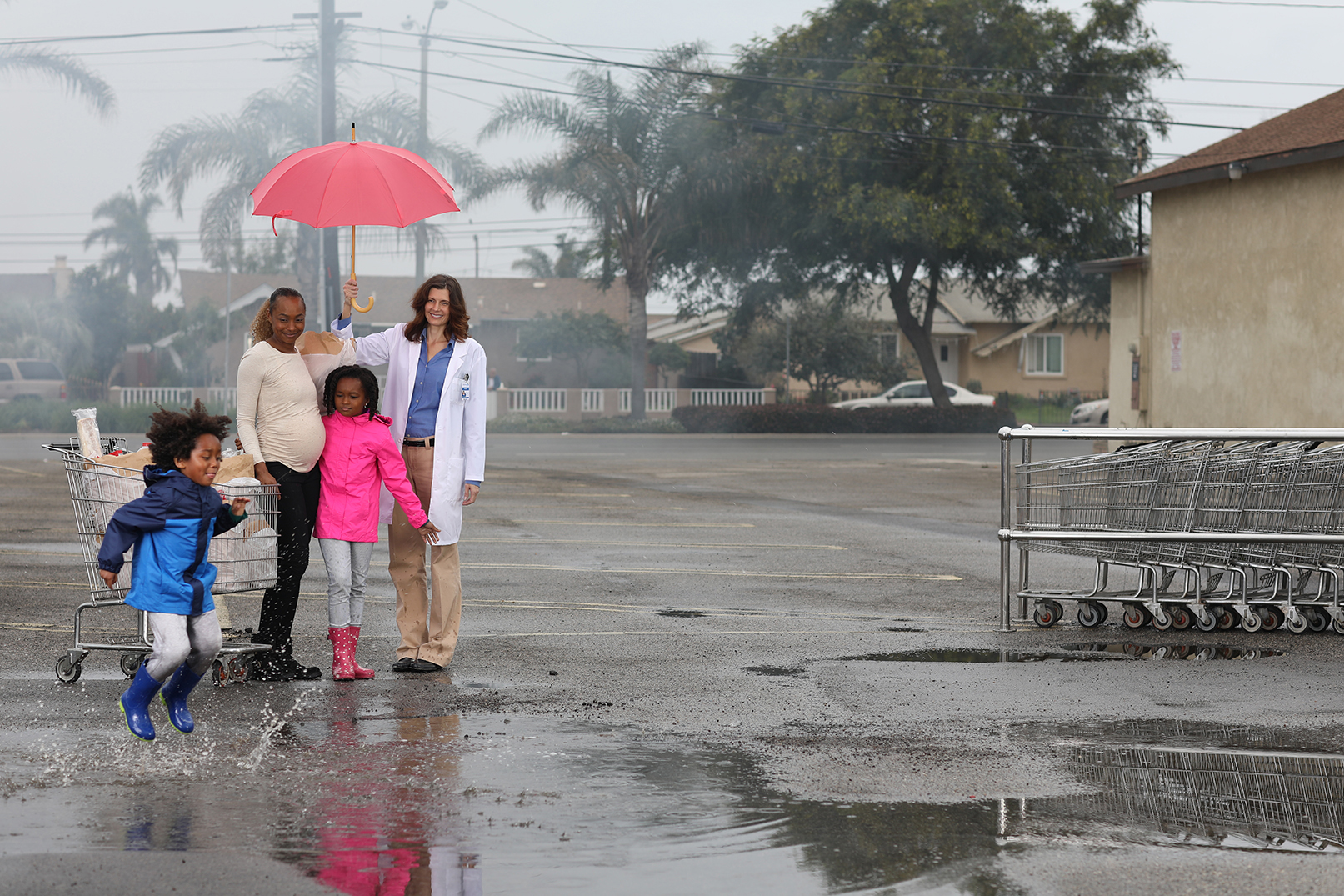 female doctor holding a pink umbrella over a family of three in rainy parking lot