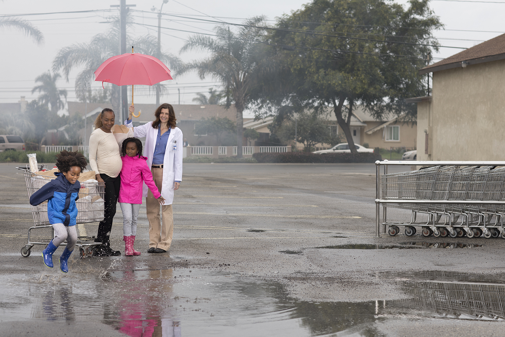 retouched female doctor holding a pink umbrella over a family of three in rainy parking lot