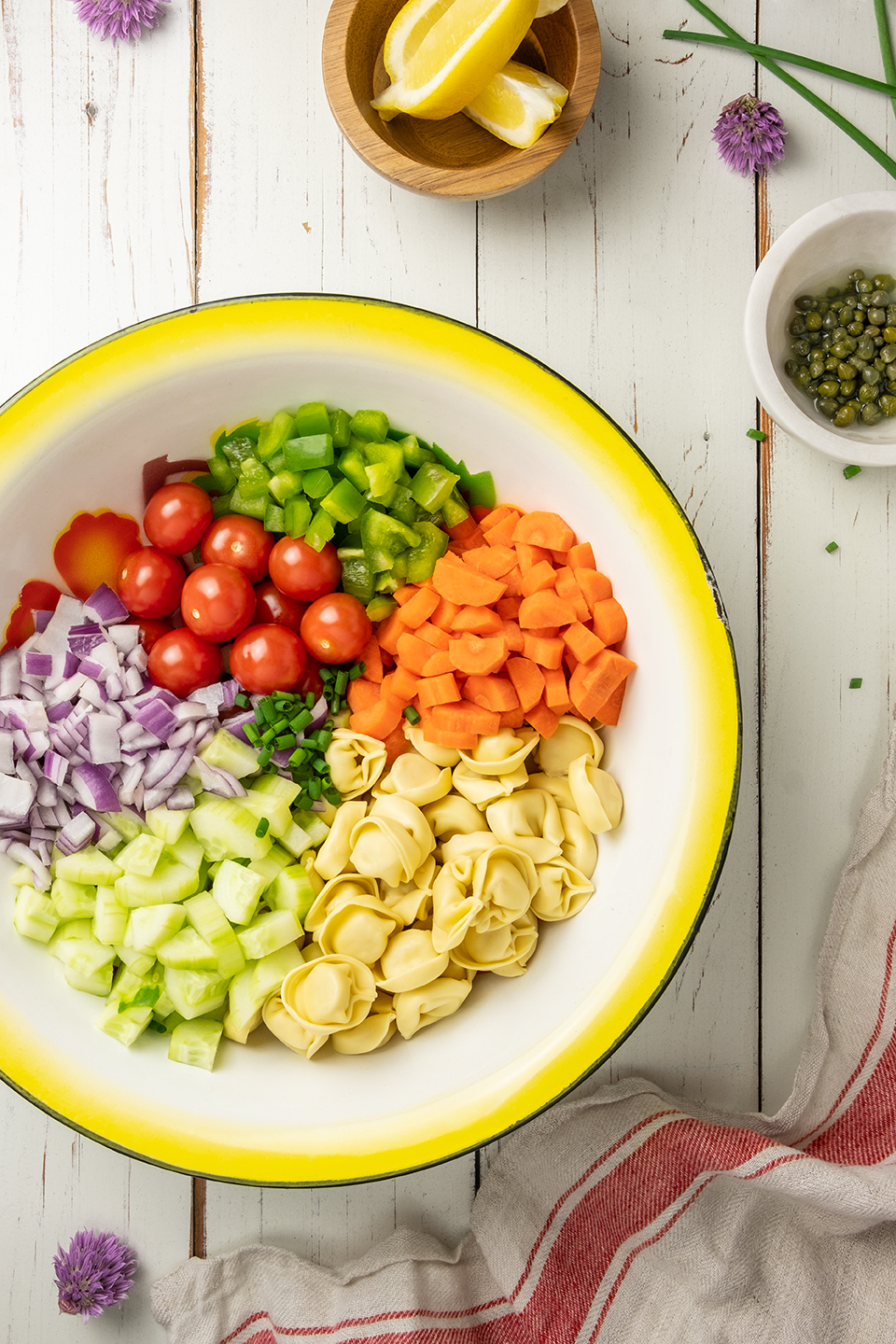 retouched ingredients for vegetable tortellini salad in a big bowl including carrots, tomatoes, and onions