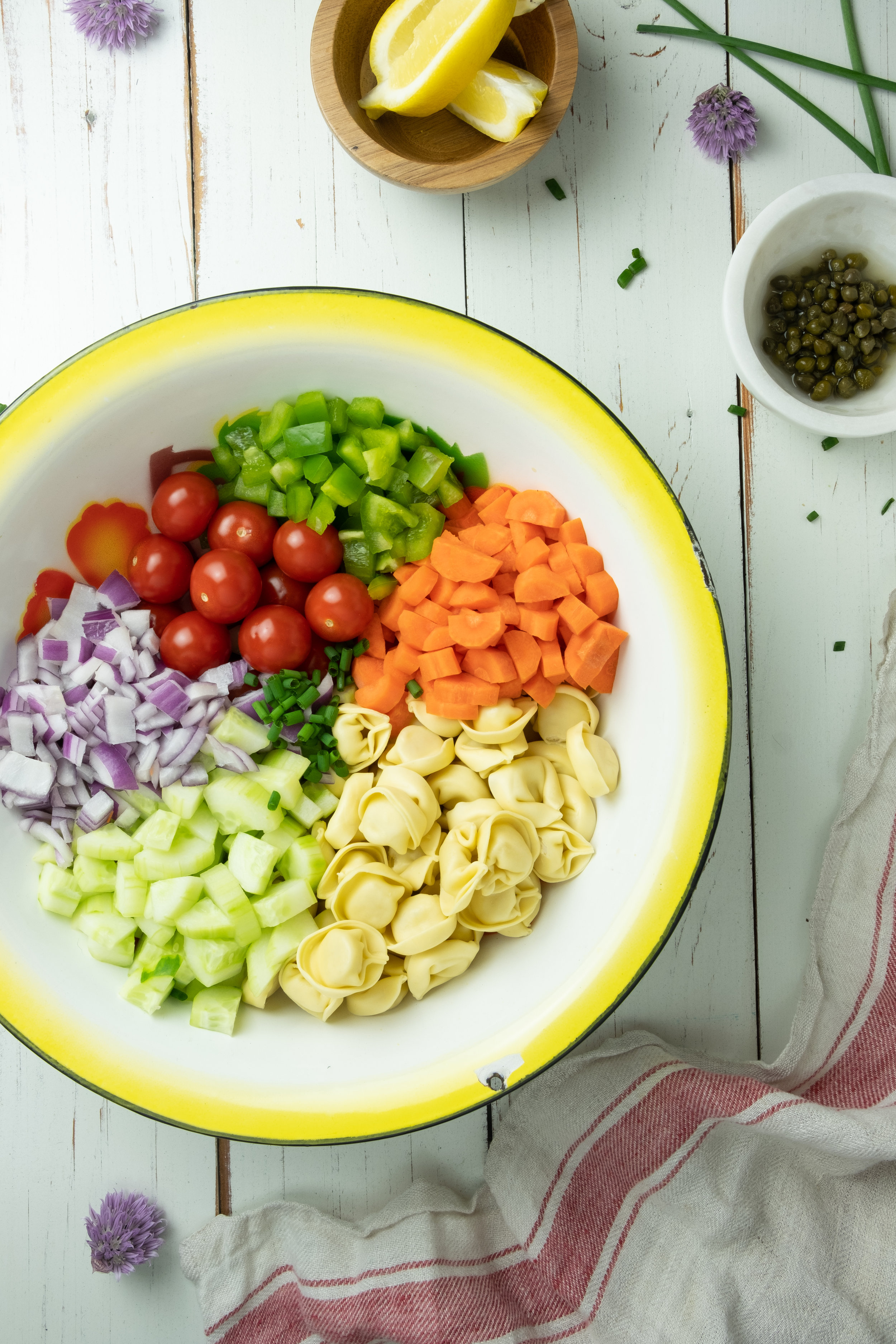 ingredients for vegetable tortellini salad in a big bowl including carrots, tomatoes, and onions