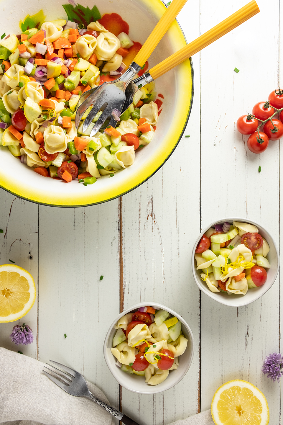 retouched serving bowl of tortellini vegetable salad on white wooden surface