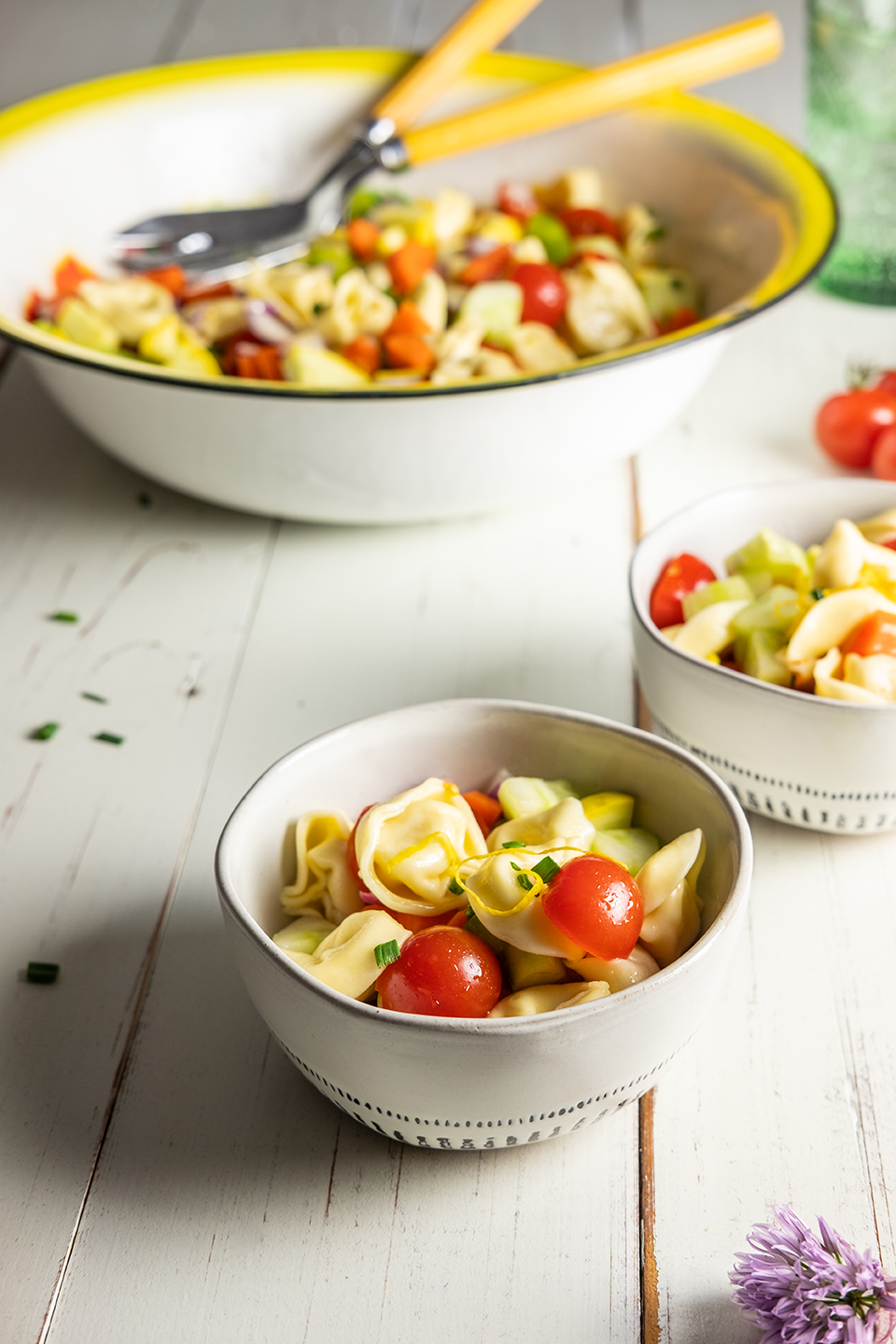 retouched Serving bowl of tortellini salad and tomatoes on white wooden surface