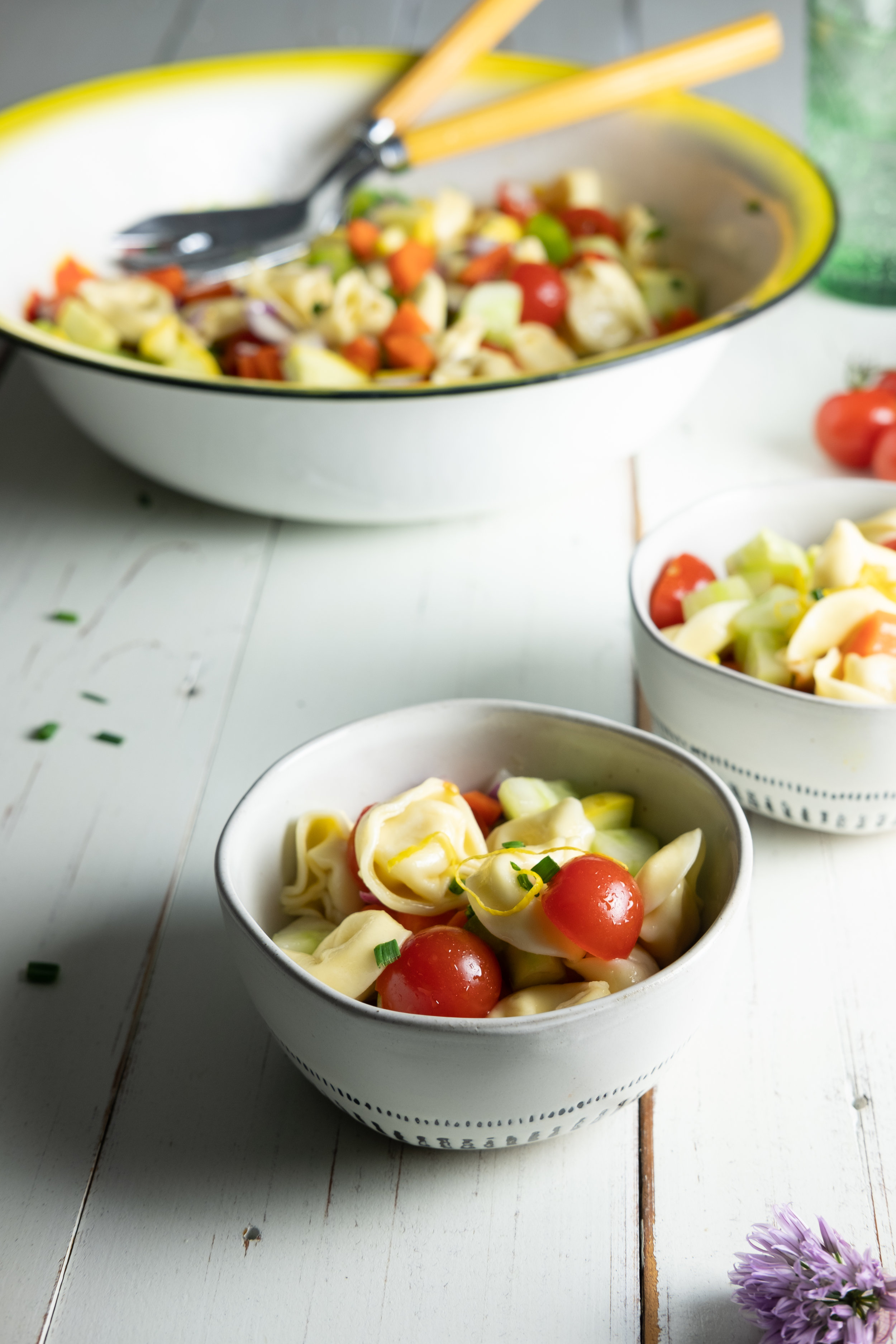 Serving bowl of tortellini salad and tomatoes on white wooden surface