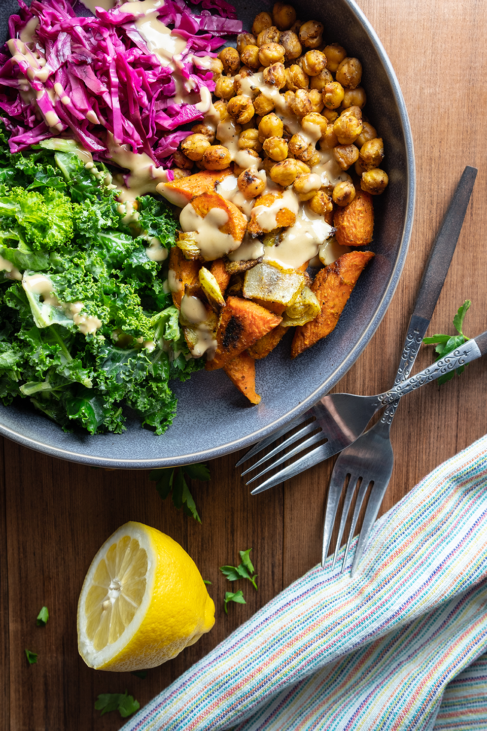 retouched  bowl of shredded cabbage, kale, and roasted chickpeas on a wooden table