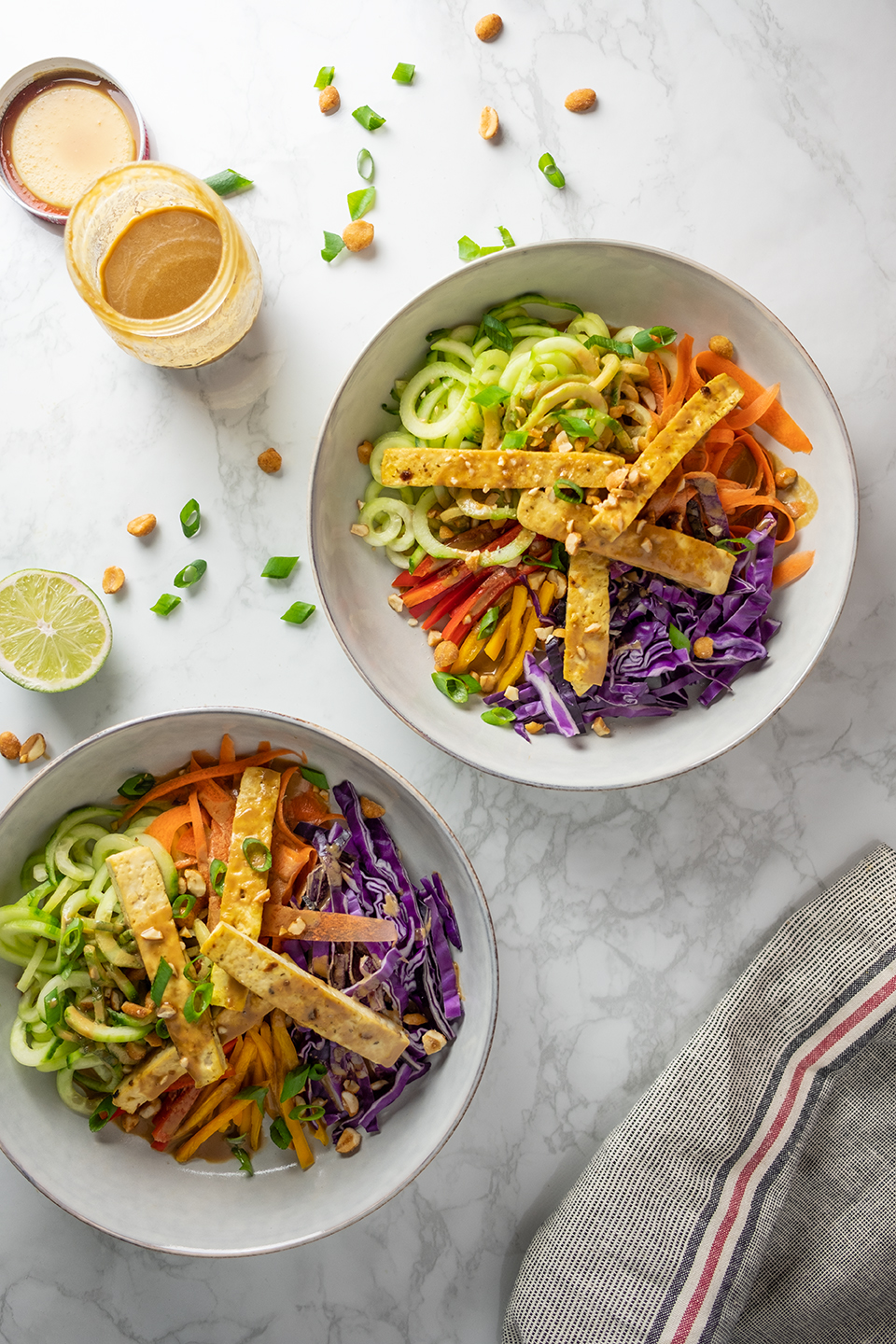 retouched bowls of tofu and veggie noodles next to an open jar of sunbutter dressing