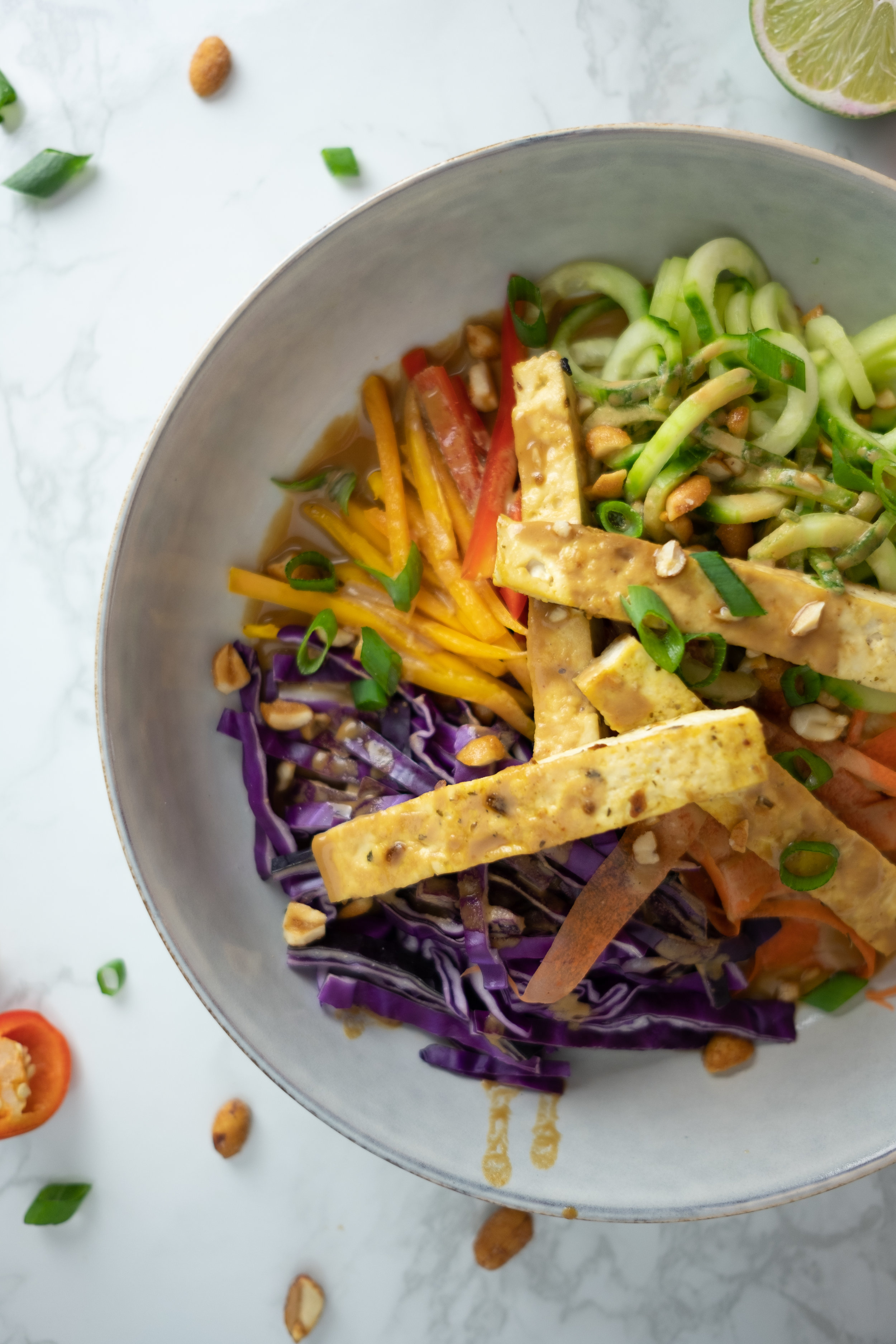 bowl of tofu and zoodles on a white background