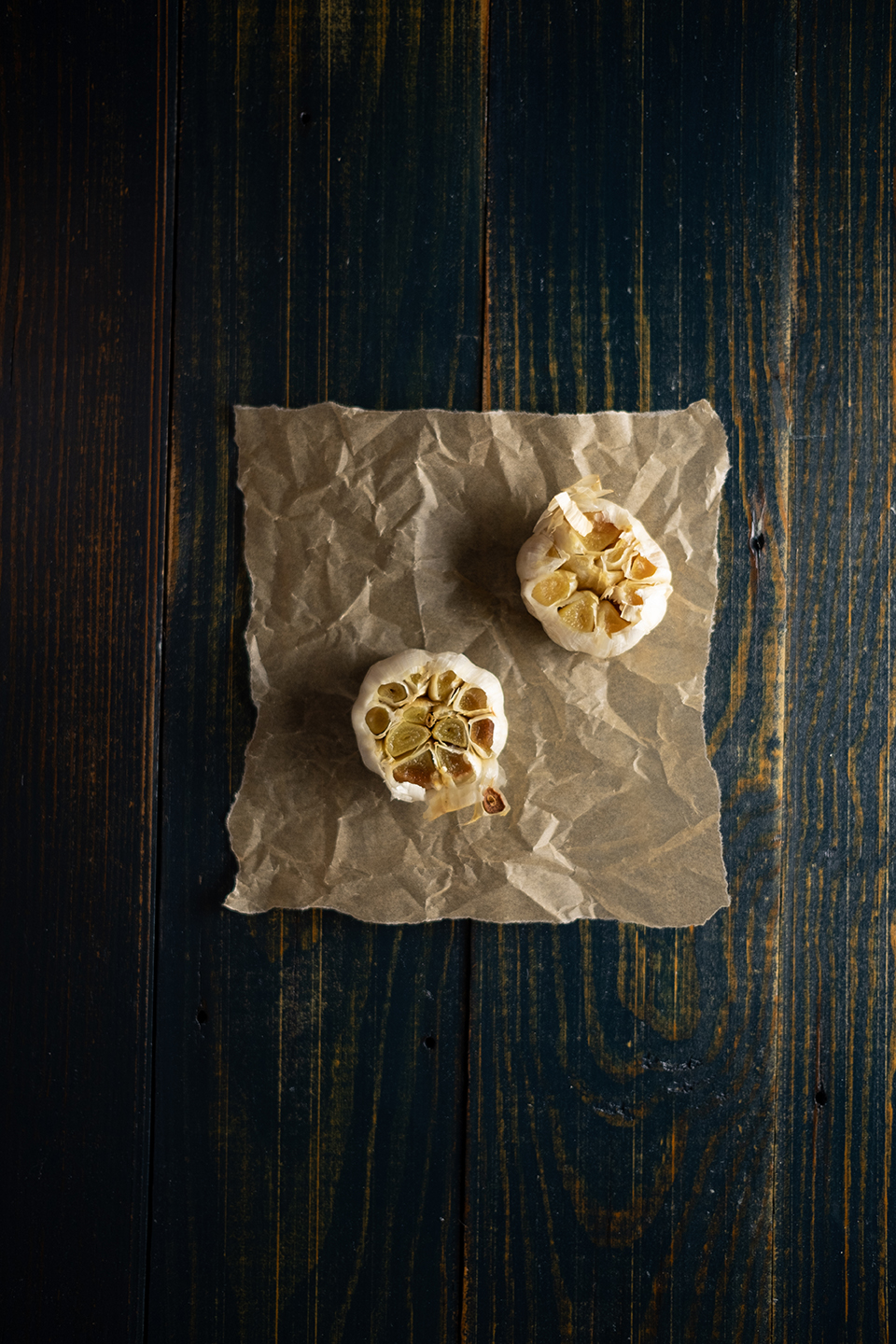 two roasted garlic bulbs on brown parchment paper