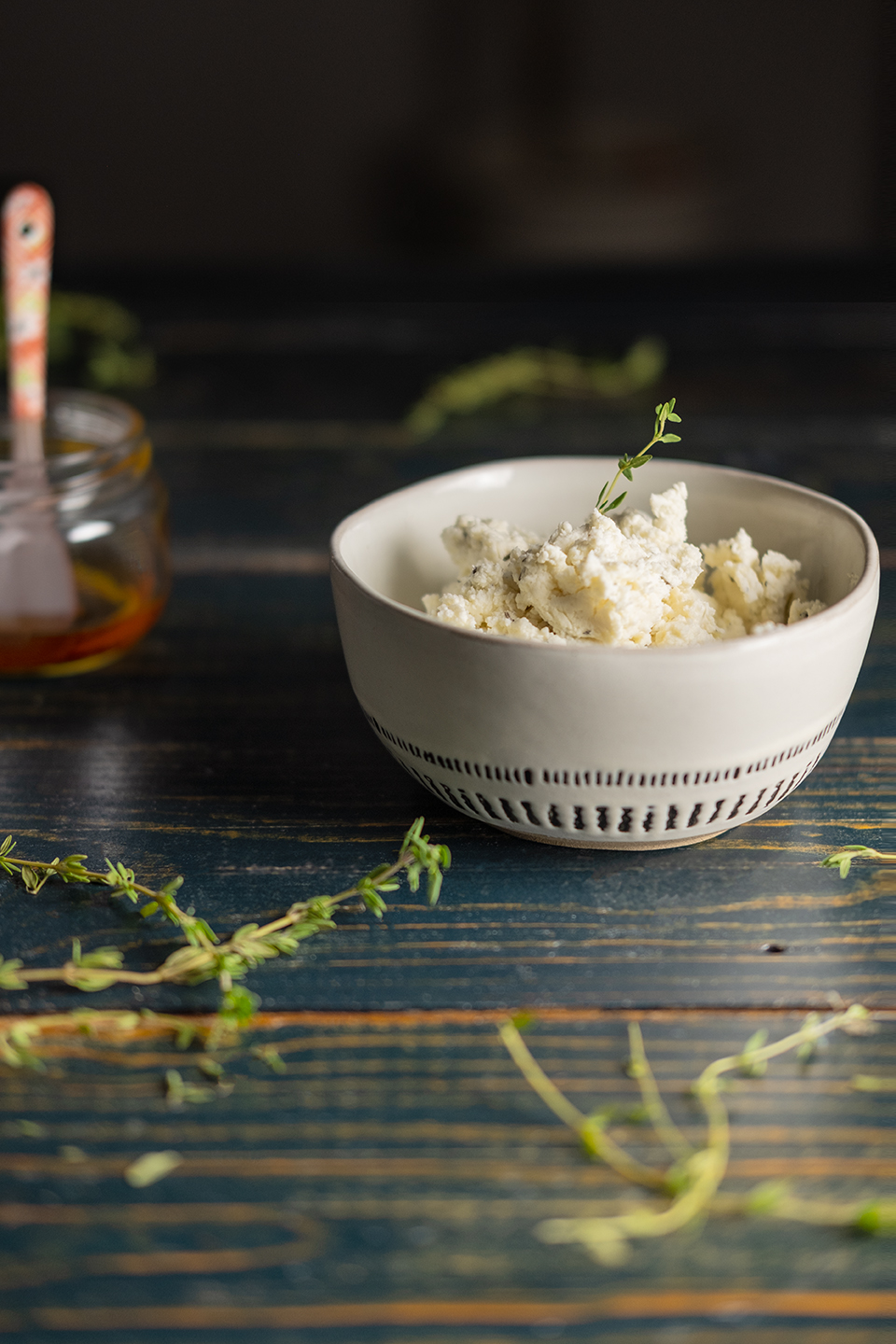 retouched honey goat cheese spread in a bowl surrounded by sprigs of fresh thyme