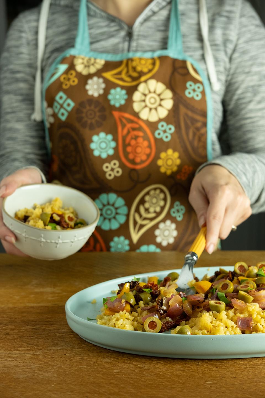 woman in floral apron serving saffron cauliflower rice