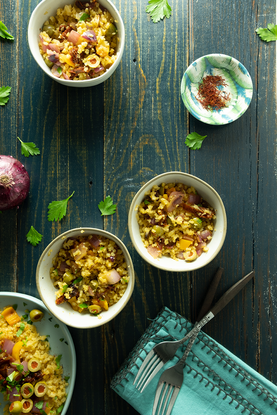 appetizer bowls of saffron cauliflower rice on a blue wooden table
