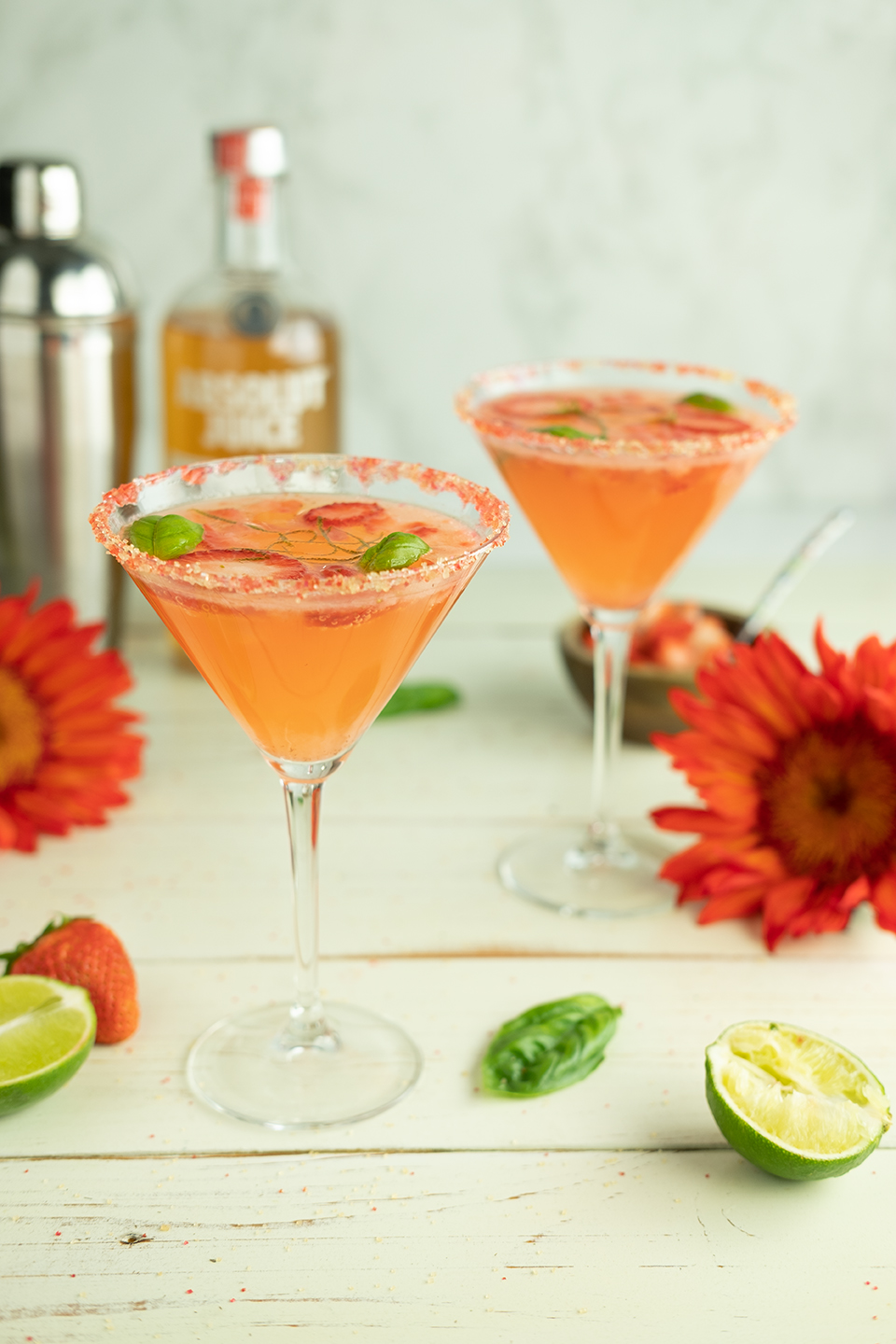 Two strawberry and basil cocktails in sugar-rimmed glasses