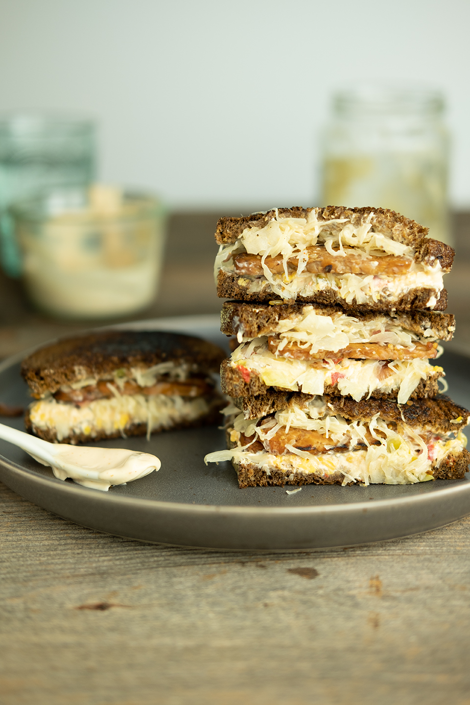 stack of vegetarian reuben sandwiches on a brown plate and wooden surface