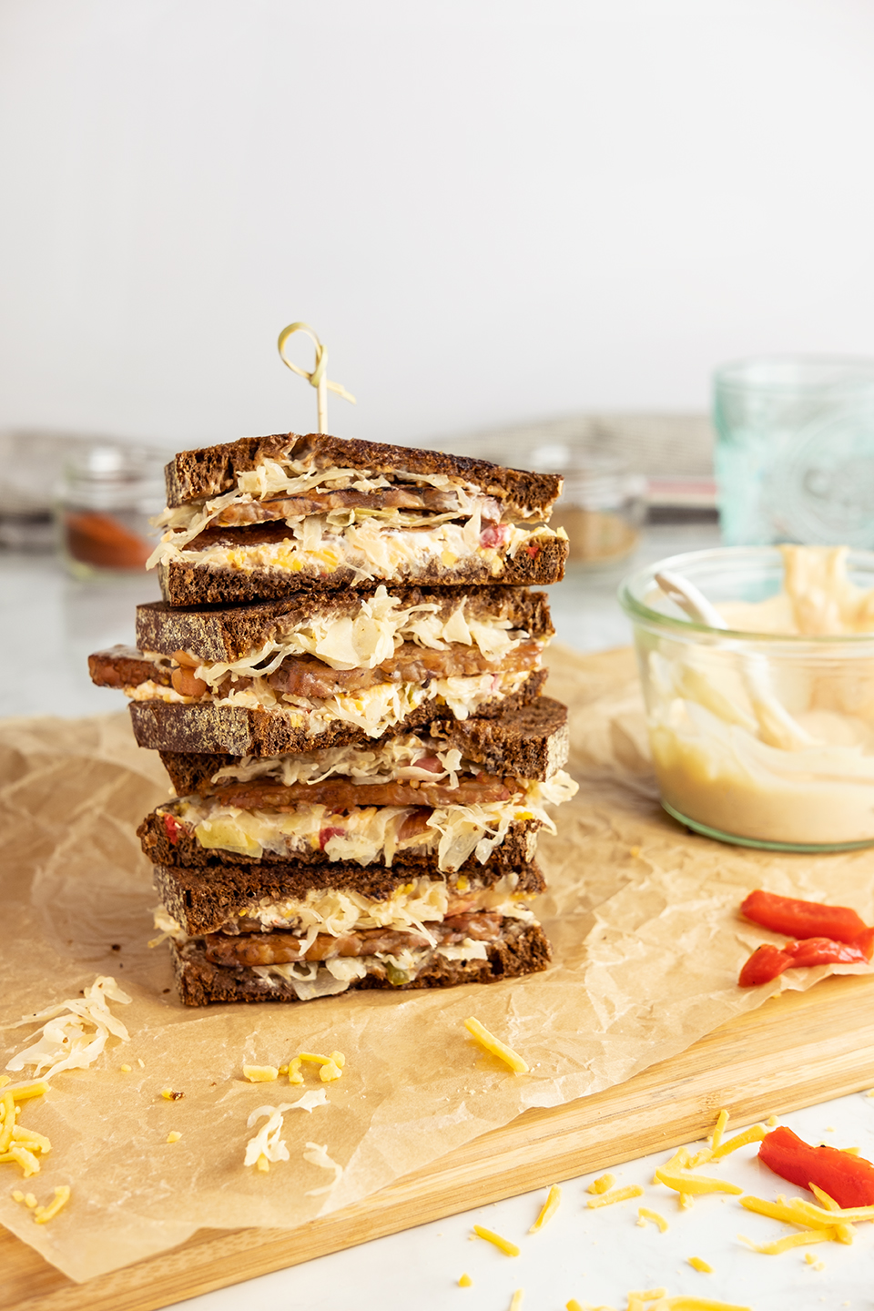 retouched stack of vegetarian reuben sandwiches on brown parchment paper and wooden cutting board