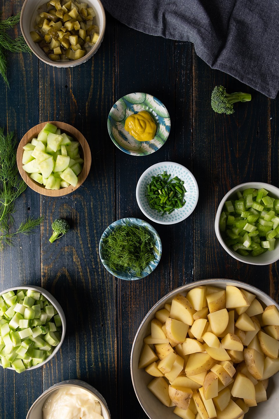 ingredients for potato and broccoli salad in decorative bowls of various sizes