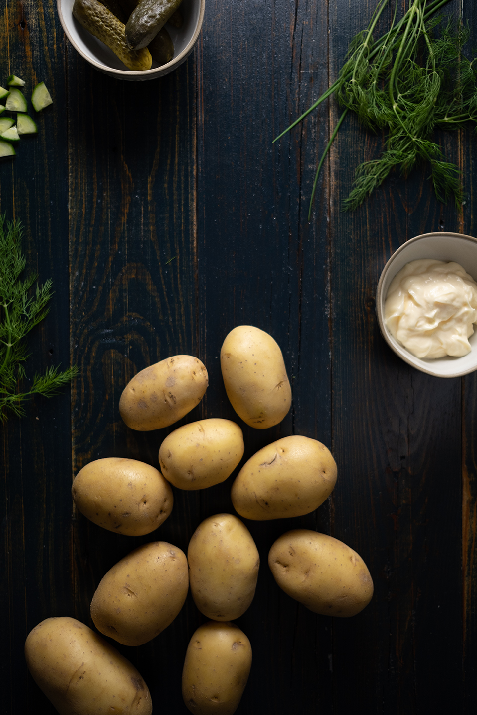 yukon gold potatoes on wooden table with potato salad ingredients