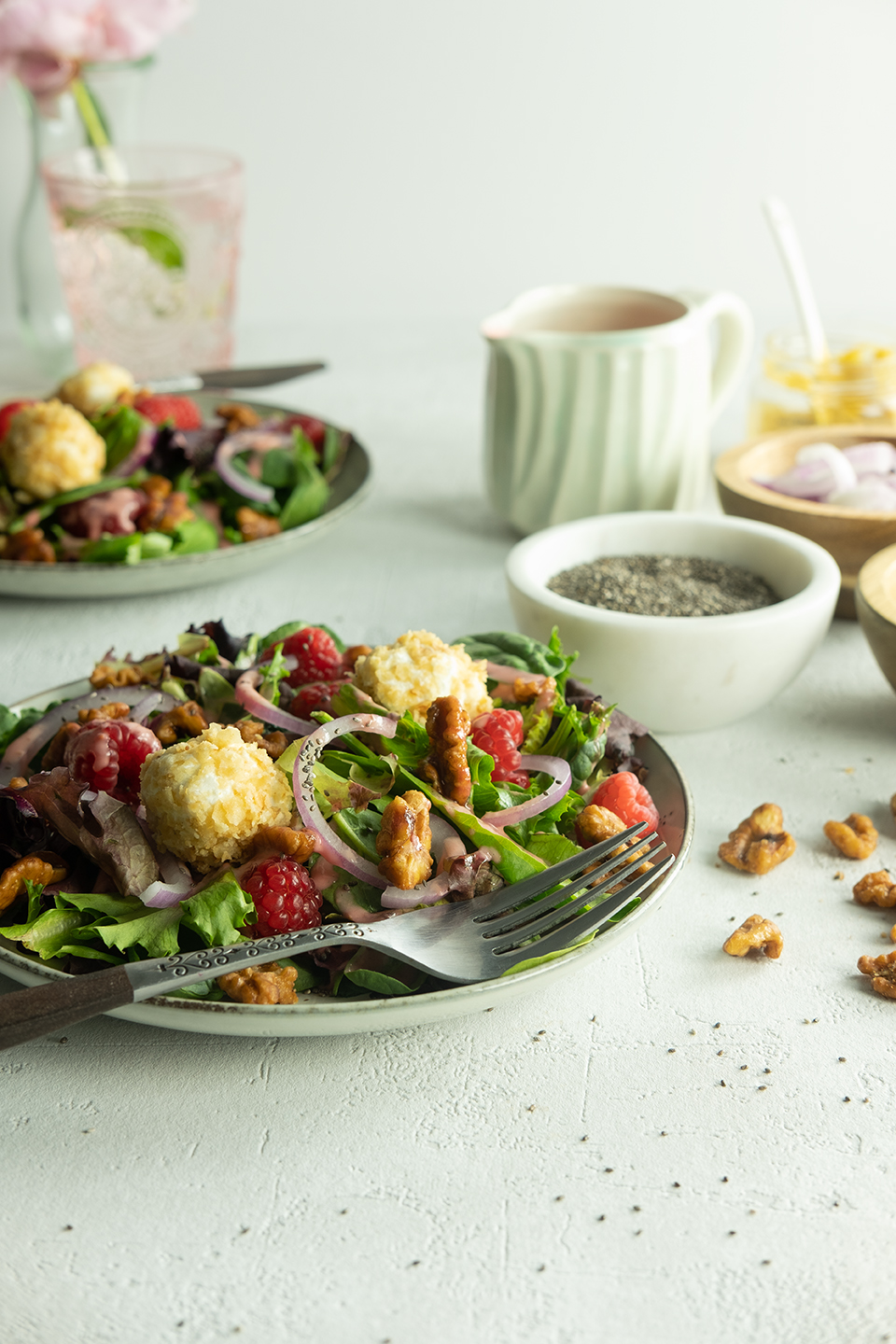 fresh summer salad with raspberry and walnuts on a white textured table