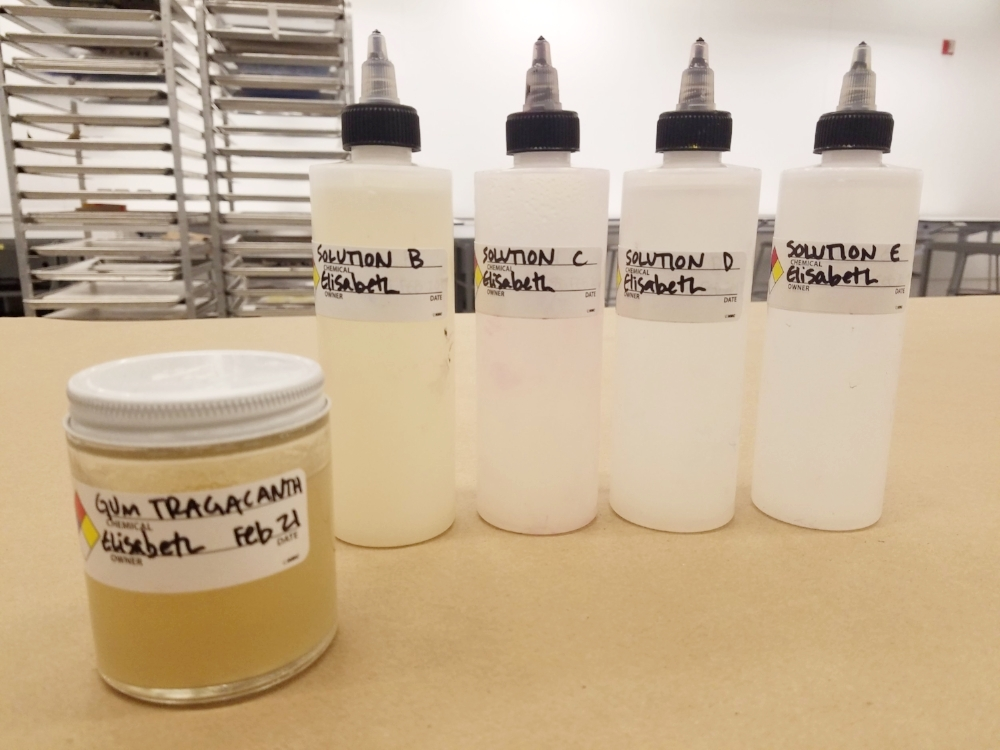 Pure Gum Tragacanth (A) in jar, and solutions B – E assembled. Notice the visible tone in Solutions B and C (33.3% concentration and 11.1% respectively) compared to the pure water look of solutions D and E (3.7% concentration and 1.2% respectively)