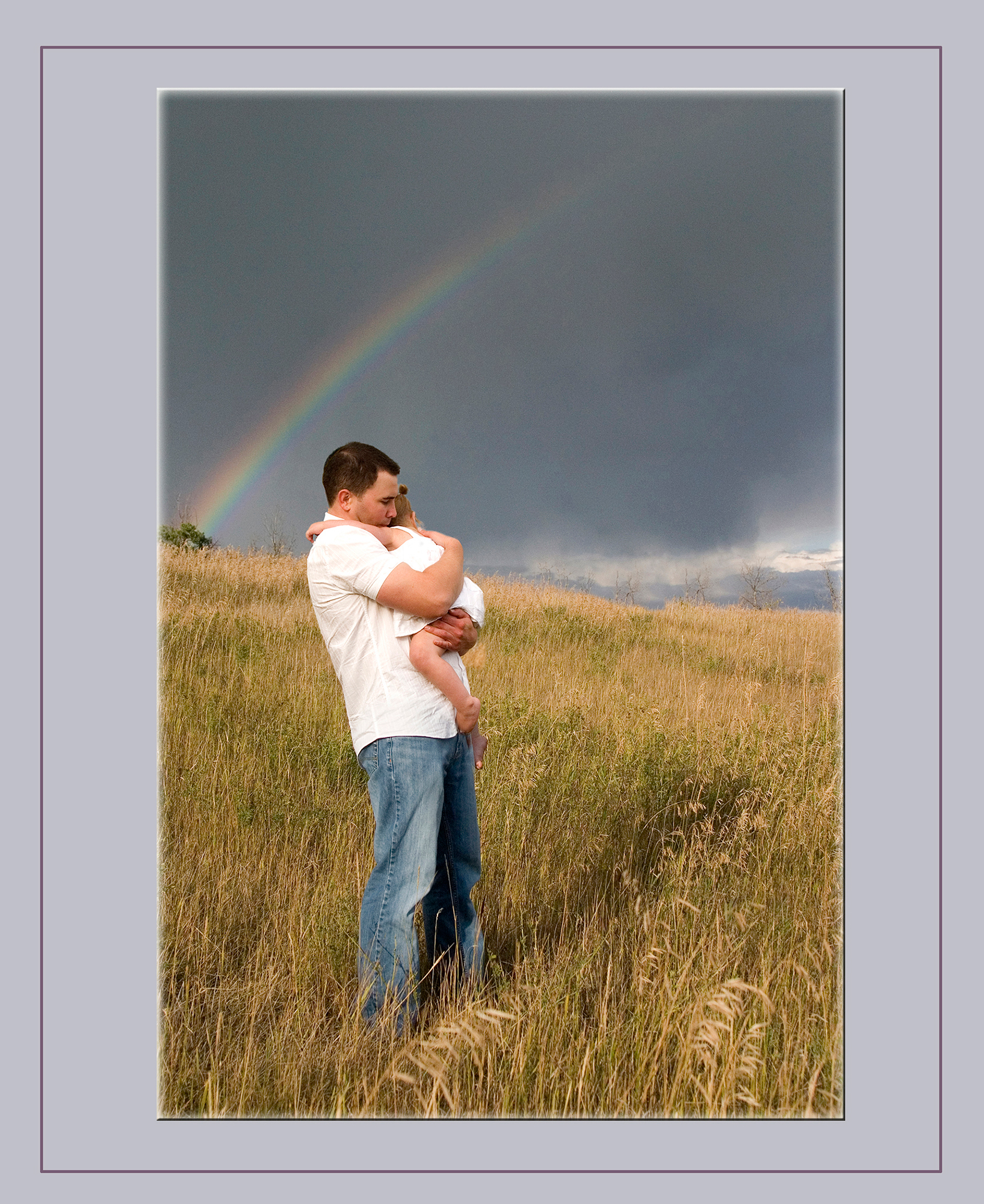 Father and Daughter standing in wheat field rainbow in background