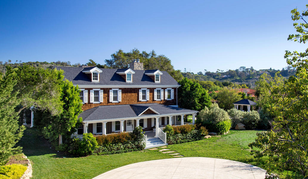 A New England-style home sits behind a tree-lined drive and gates on Featherhill Road in Montecito