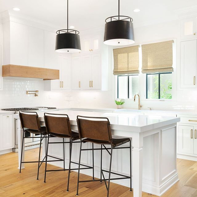 This sleek kitchen includes white painted maple cabinets, aged iron pendants, and quartz countertops. The stained hickory hood accent, white oak floors, and black windows provide contrast to complete the design.  Built by @ramagecompany  Interiors by @lcinteriors  Cabinets by @century_entertainment  Architecture by @c3studiollc  #ramagecompany #interiordesign #interiors #houseandhome #homeinspo #nortoncommonslife #housebeautiful #traditionalhome #architecture #luxuryhomes  #Italianate #whitekitchen #kitchen #kitcheninspo #quartz #leather #bourbon #brass