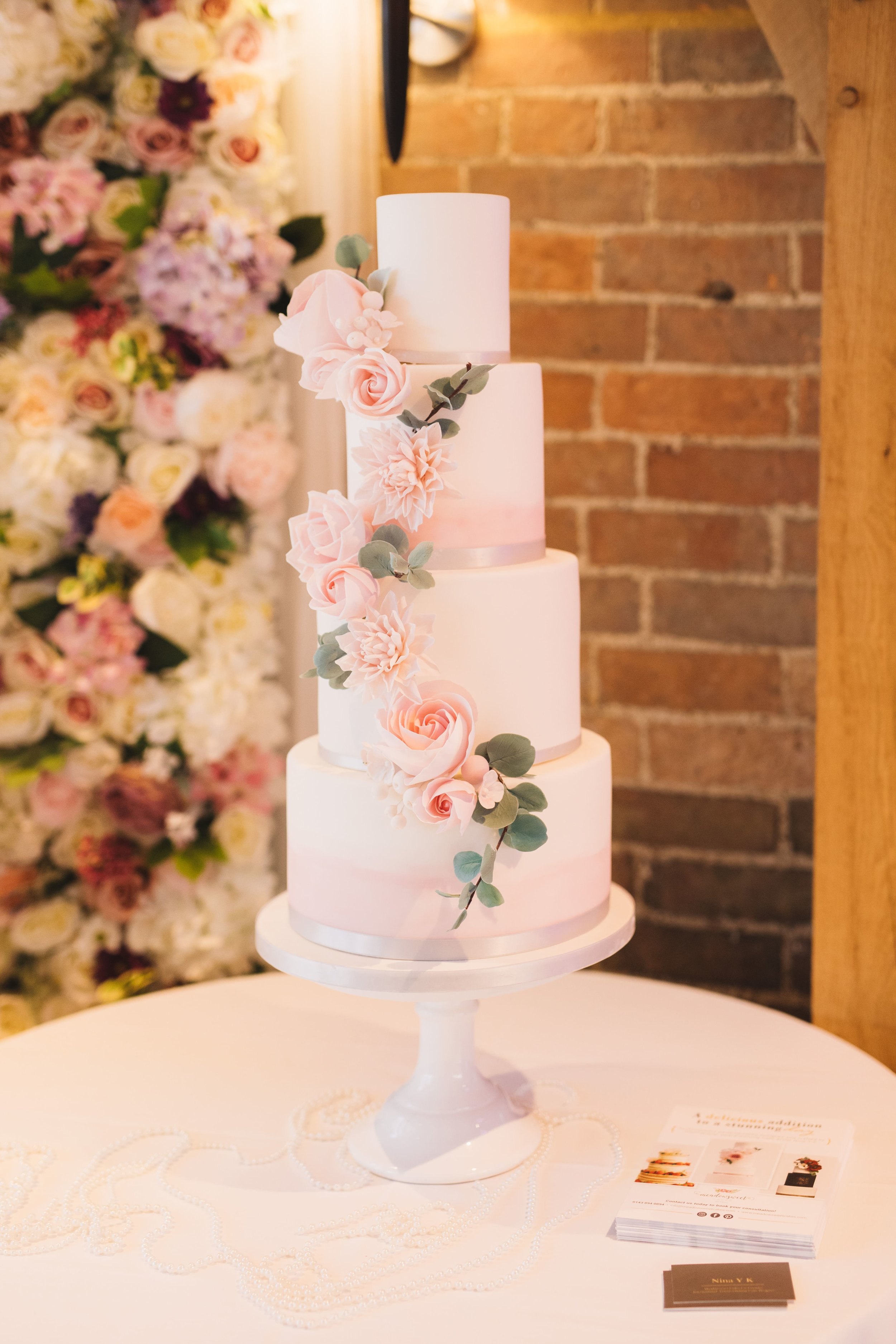 Floral wedding cake with blush watercolour effect and sage foliage by Meadowsweet Cakes, set up at Bassmead Manor Barns. Photography by Cat Lane Photo