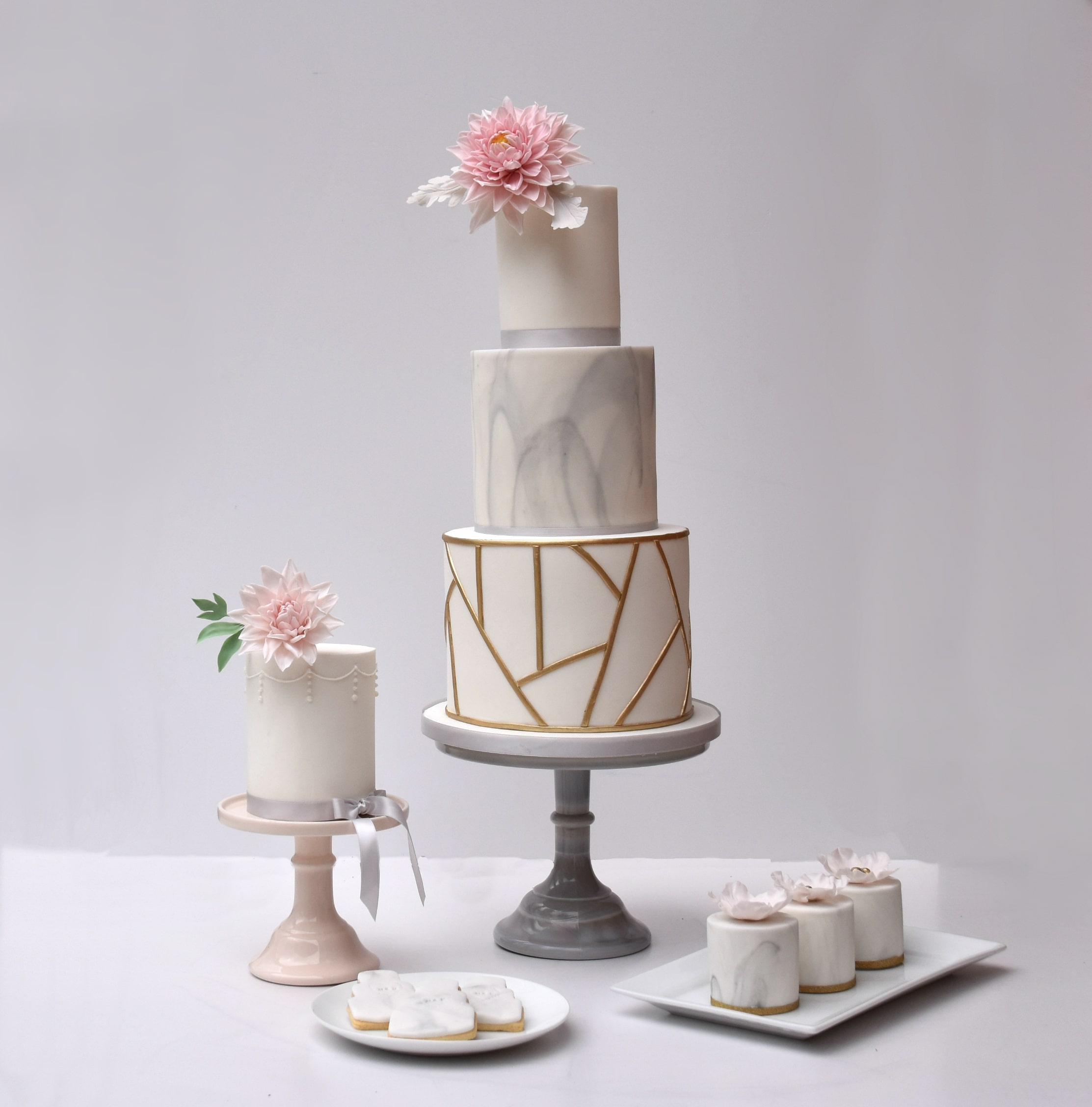 Luxury wedding dessert table with modern 3 tiered cake, mini cakes, single cake, iced biscuits and sugar flowers. Modern design with gold geometric pattern, marble grey and sugar dahlia. Cake by Hertfordshire wedding cake company Meadowsweet Cakes.