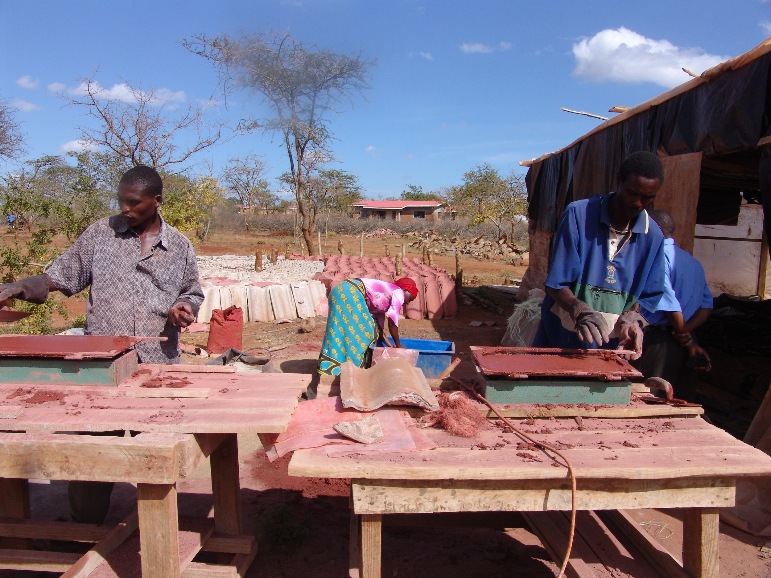 Construction workers learn to make clay roofing tiles at Nyumbani Village in Kenya