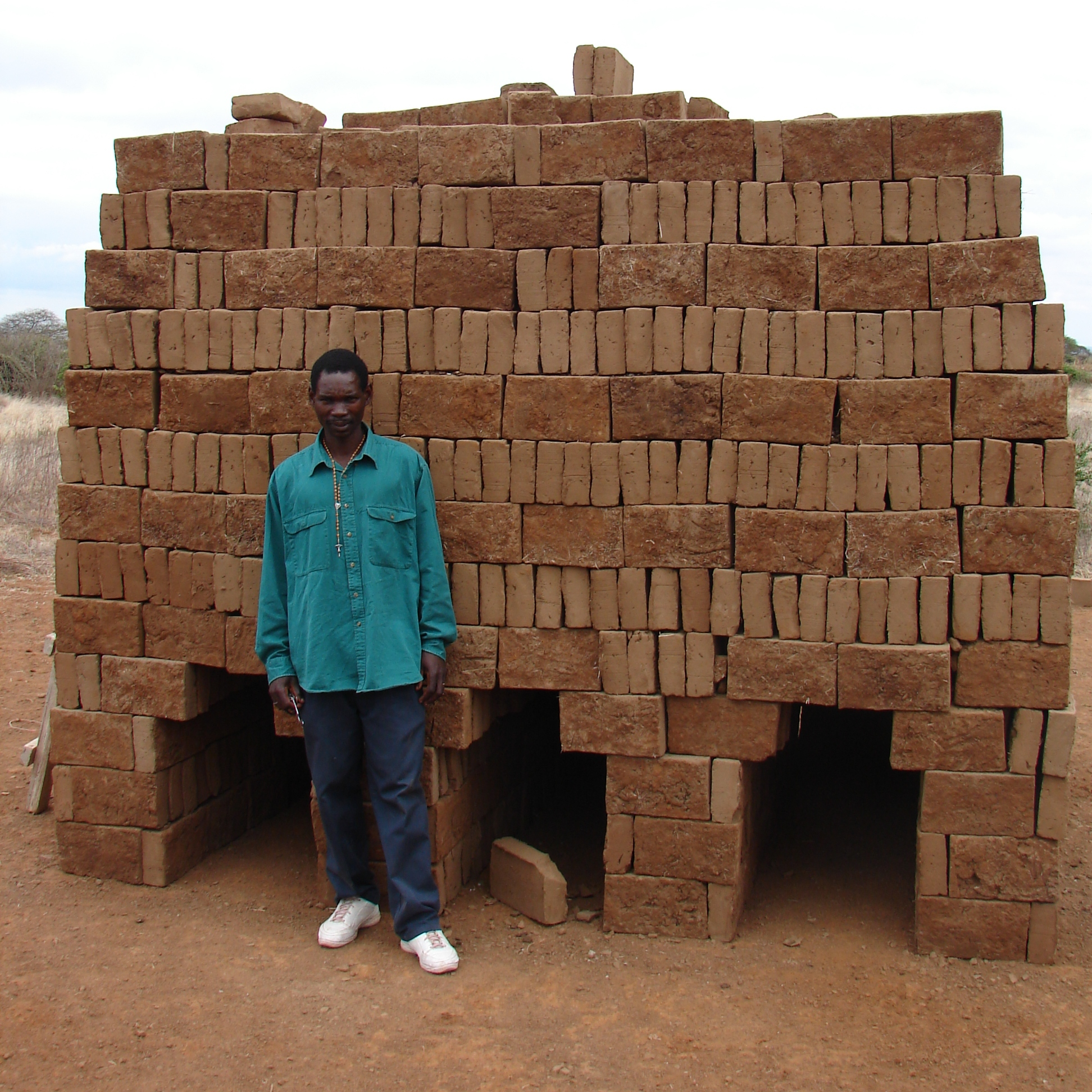 A mason stands in front of a pile of clay bricks - Tanzania
