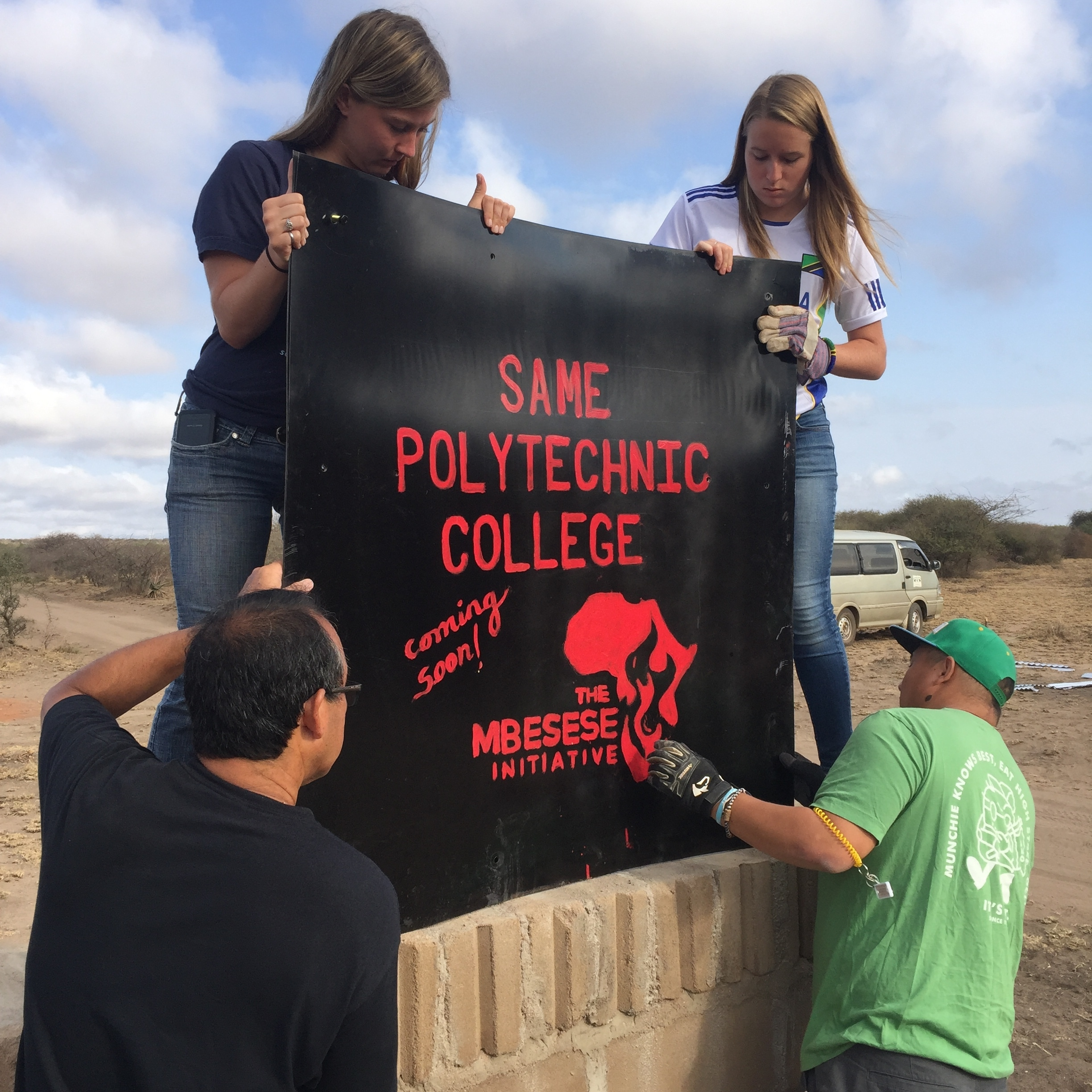 The 2017 Cal Poly team lifts one of the welcome signs into place