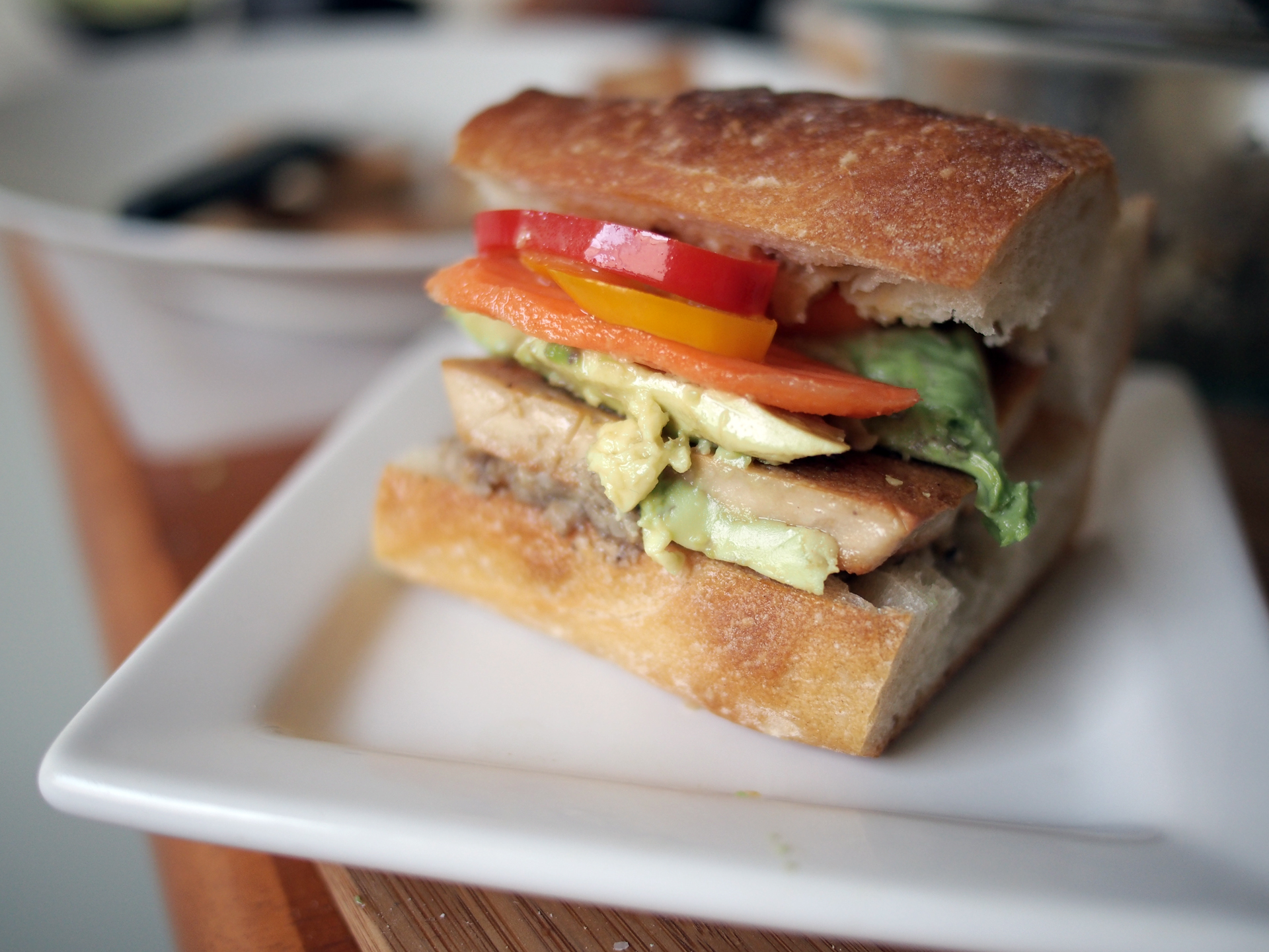 Banh mi torta with cha lua chay, mushroom cashew pate, avocado, pickled carrots, pickled sweet peppers, and sriracha allioli