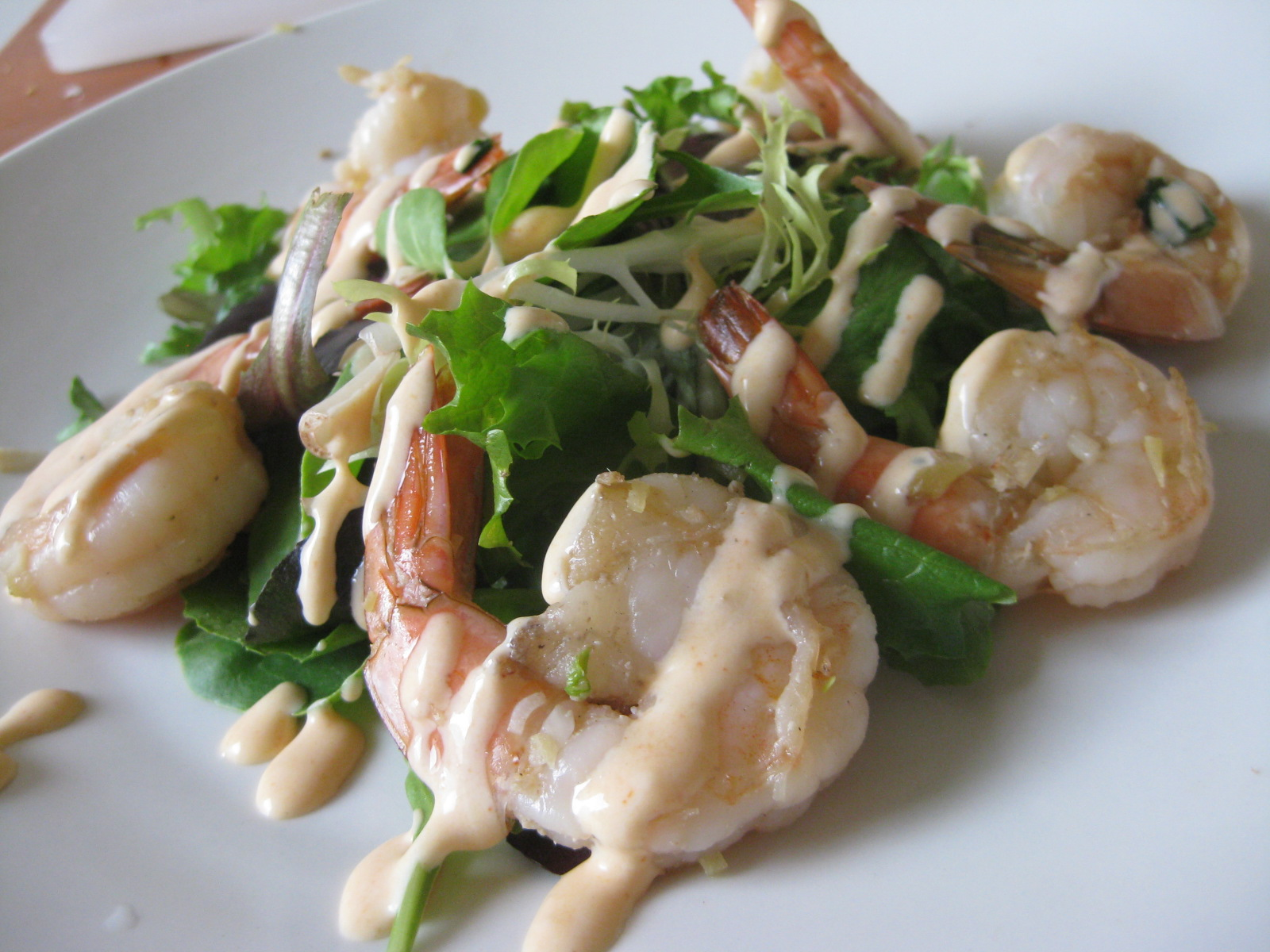 Garlic stir-fried shrimp over mixed greens with Sriracha-lime dressing.
