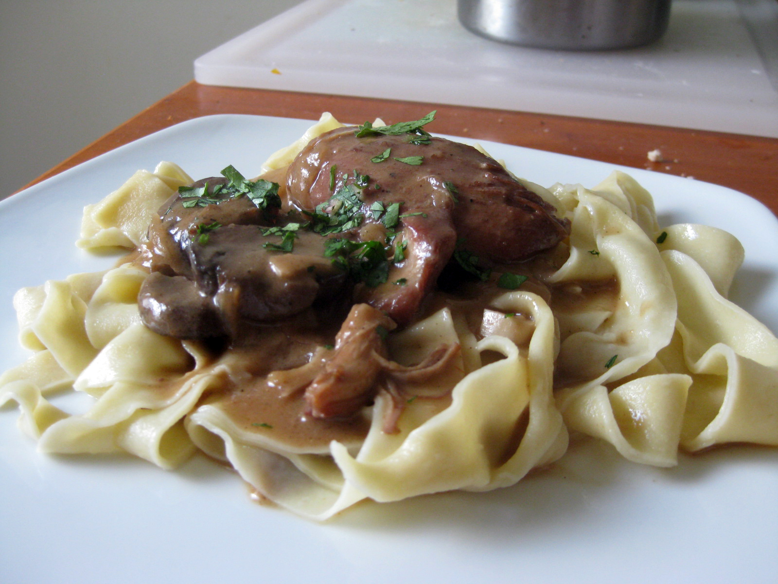 Chicken braised in burgundy wine, stock, dark soy sauce, and coconut milk with onions, garlic, and mushrooms served with fresh pasta
