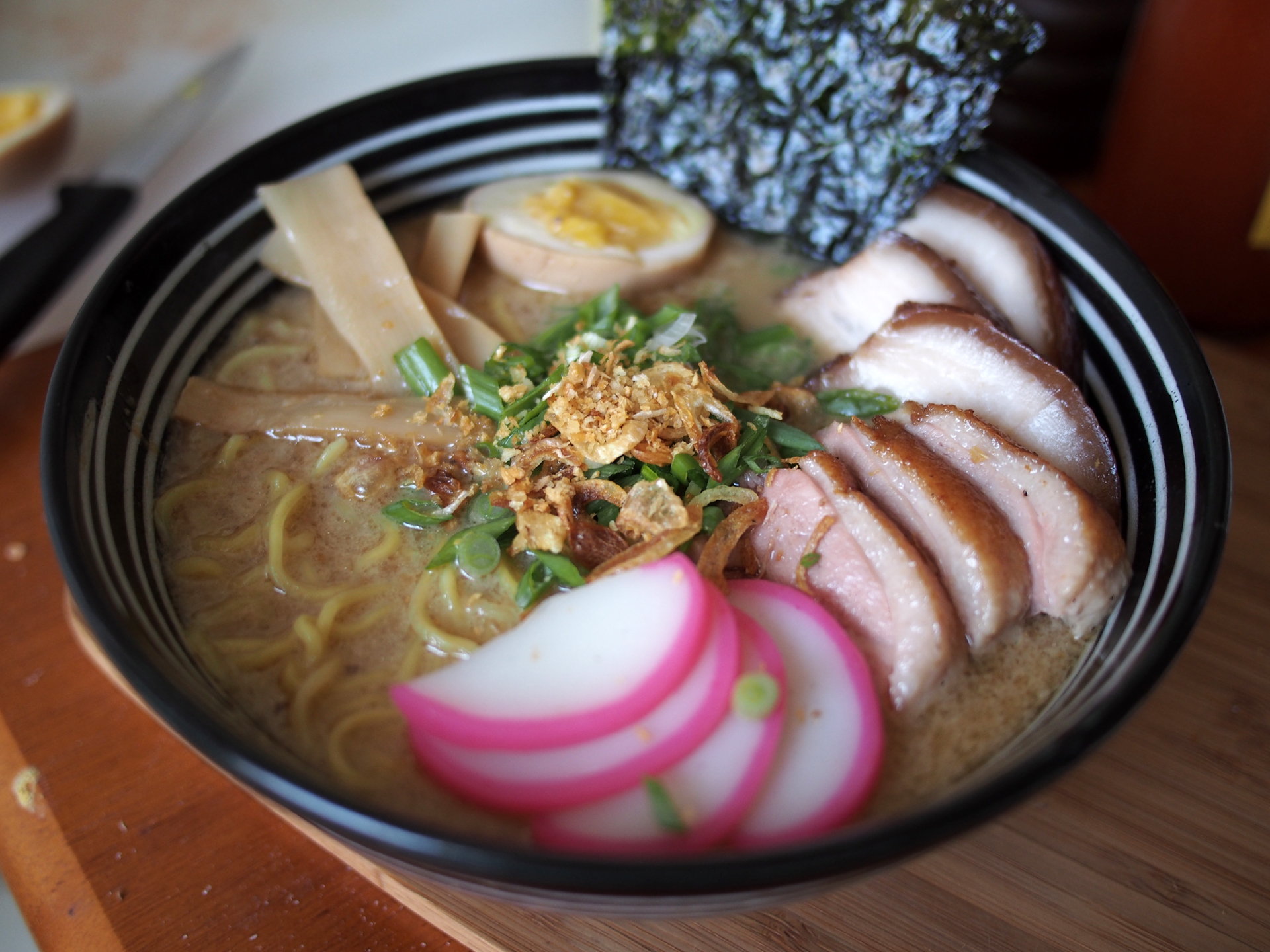 Tonkotsu/Duck ramen with sous vide pork belly chashu, sous vide duck breast, fish cake, and seasoned medium-boiled egg topped with menma, green onion, fried shallot, fried garlic, and nori strips.