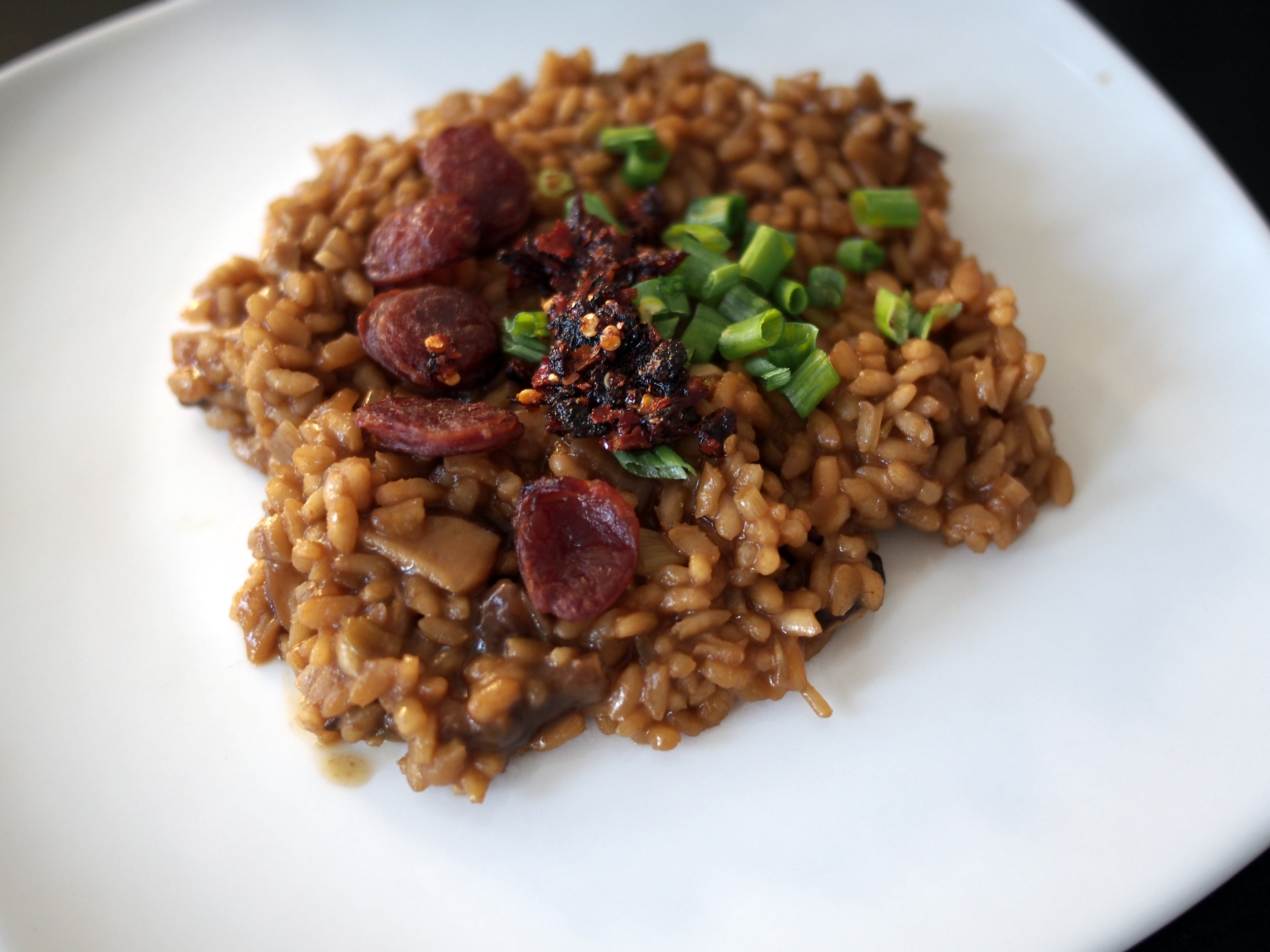 Risotto with soy sauce, shiitake mushrooms, lap cheong sausage, scallions, and chili crisp sauce