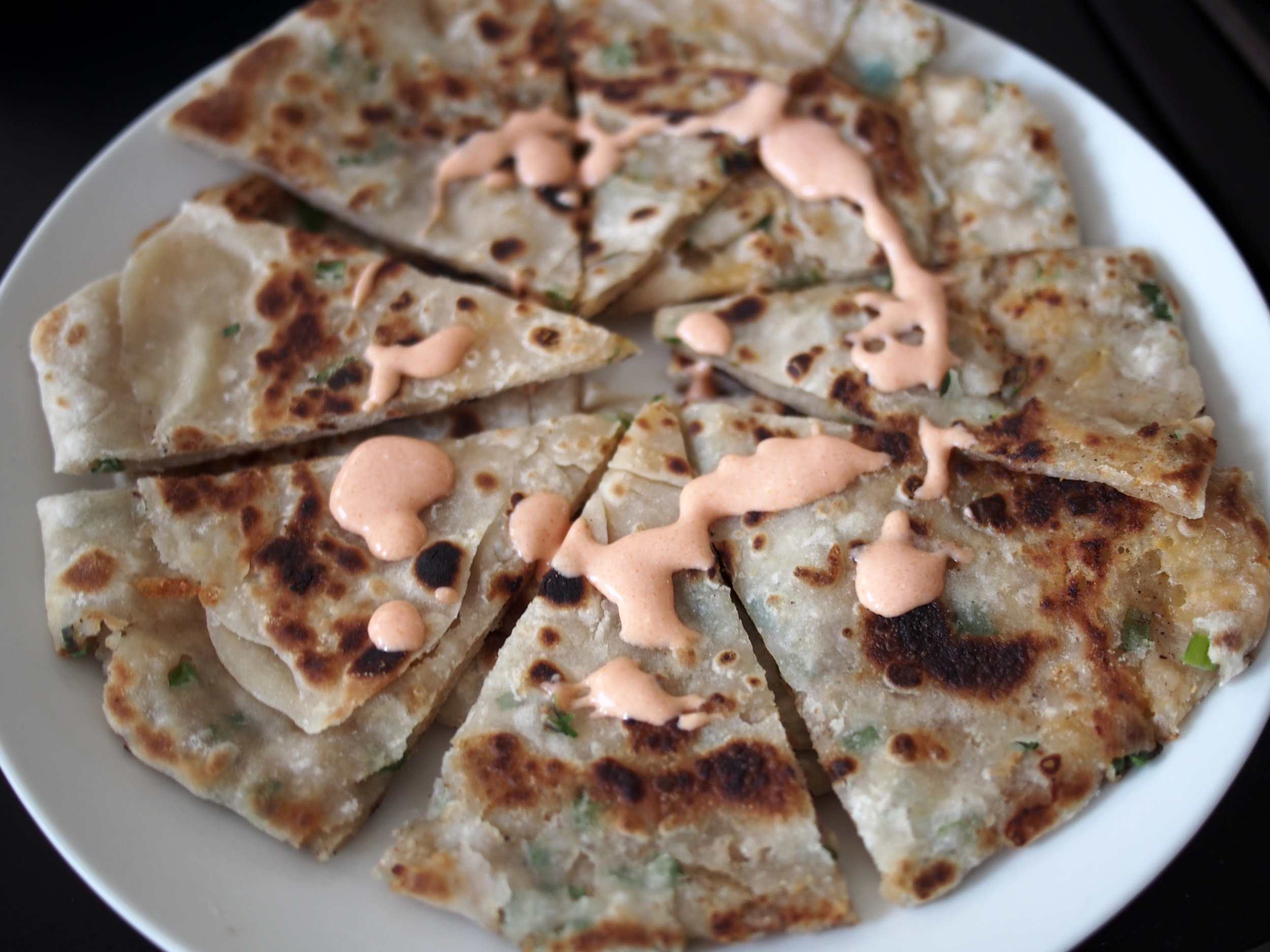 Scallion pancake stuffed with cheddar and potato and sriracha crema Salvadorena