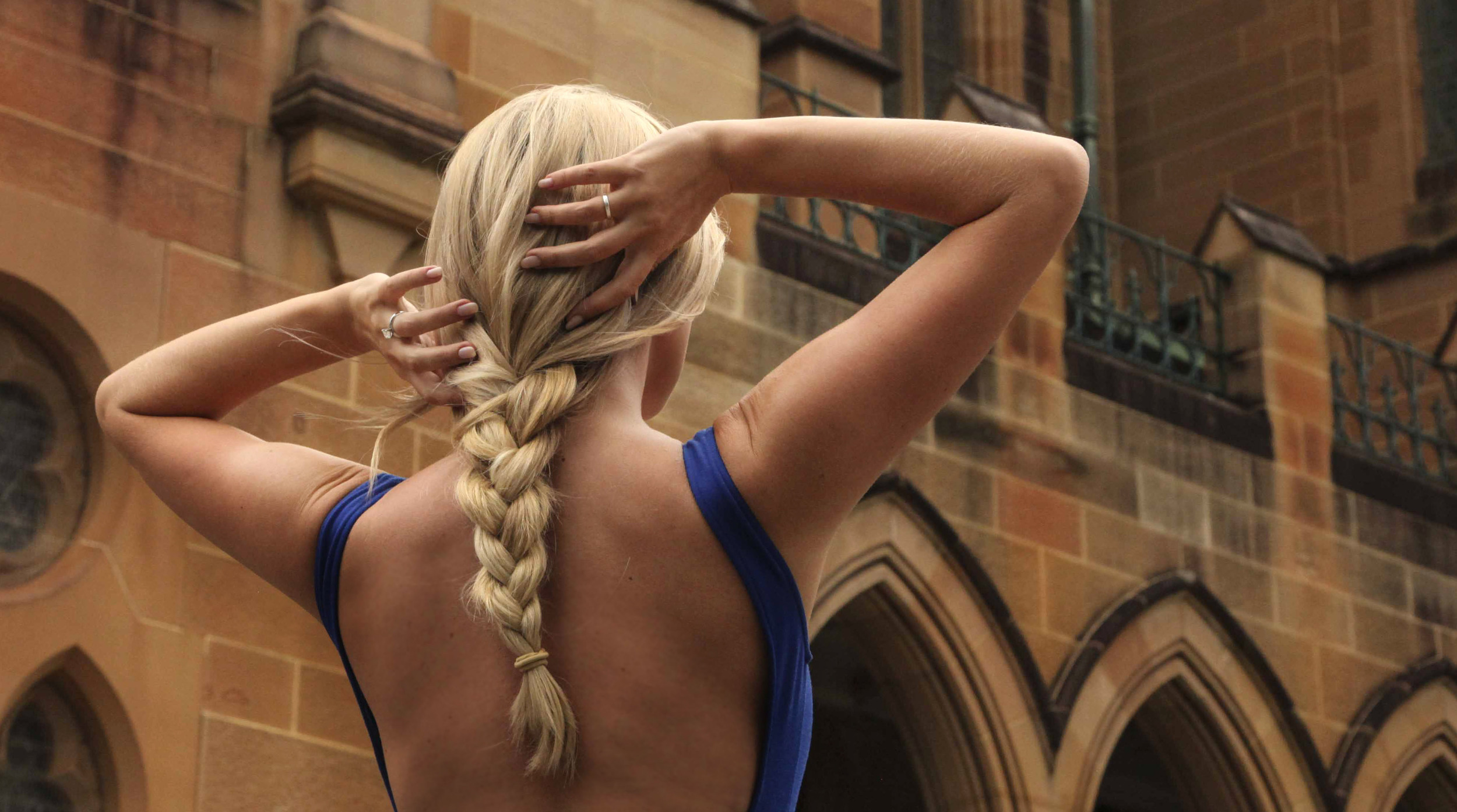 Hands up, blue dress and blonde braid