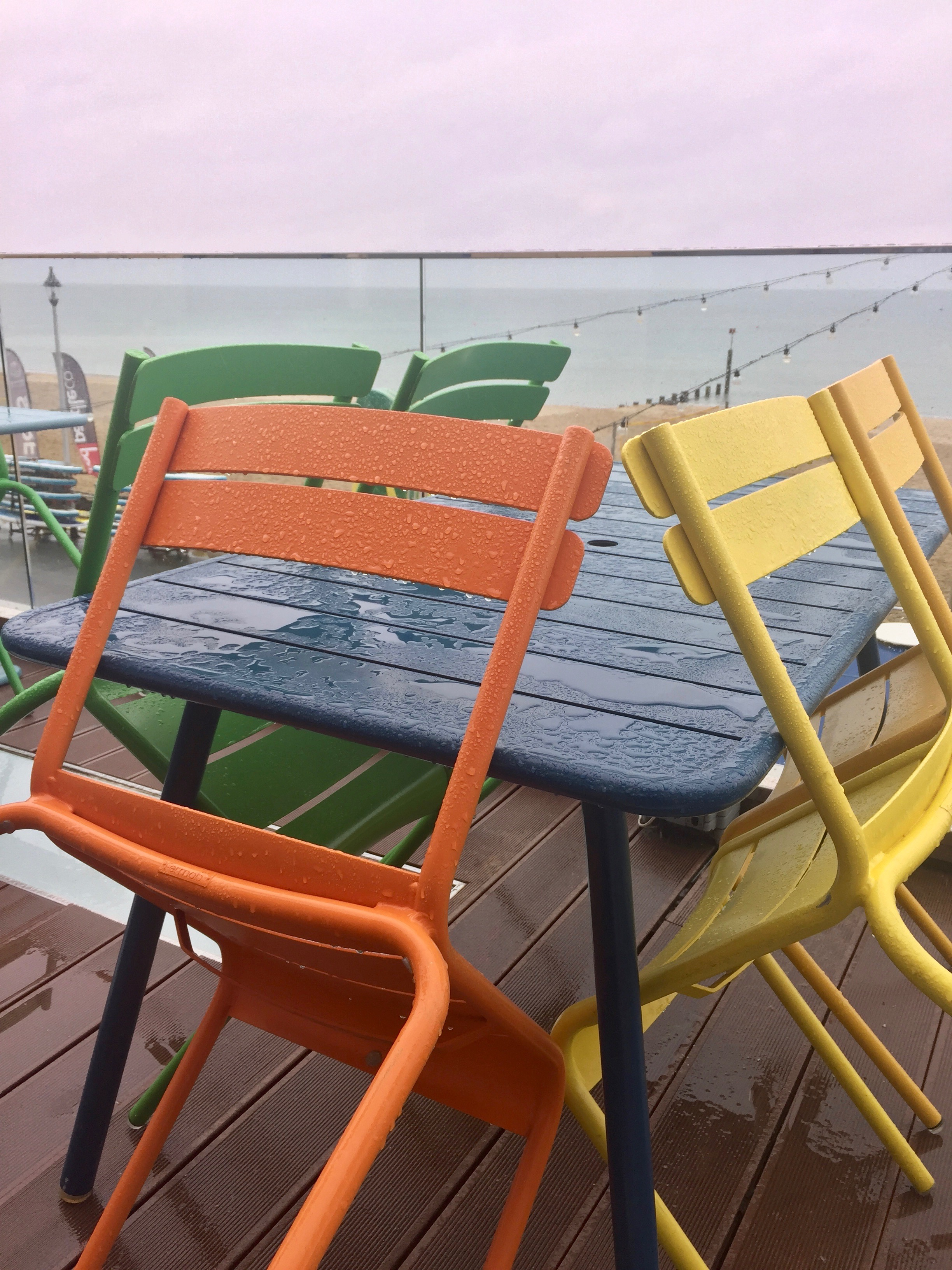 Beach cafe in the rain. Pretty chairs.
