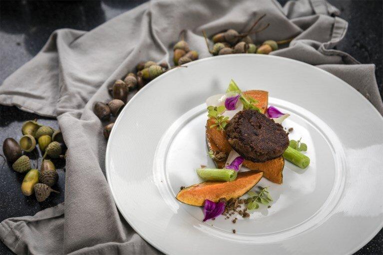 Samen met veganistisch chef-kok Pieter-Jan Lint werkt Brumagne aan een kookboek. Deze eikelburger komt daar alvast in voor.  FOTO: GUY PUTTEMANS