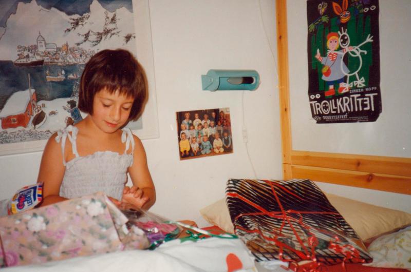 Meg som 7 åring. Mulig dette var en bursdag, men å åpne gaver i senga eller i sofaen med dyne og pyjamas har blitt fast tradisjon. Foto: mamma