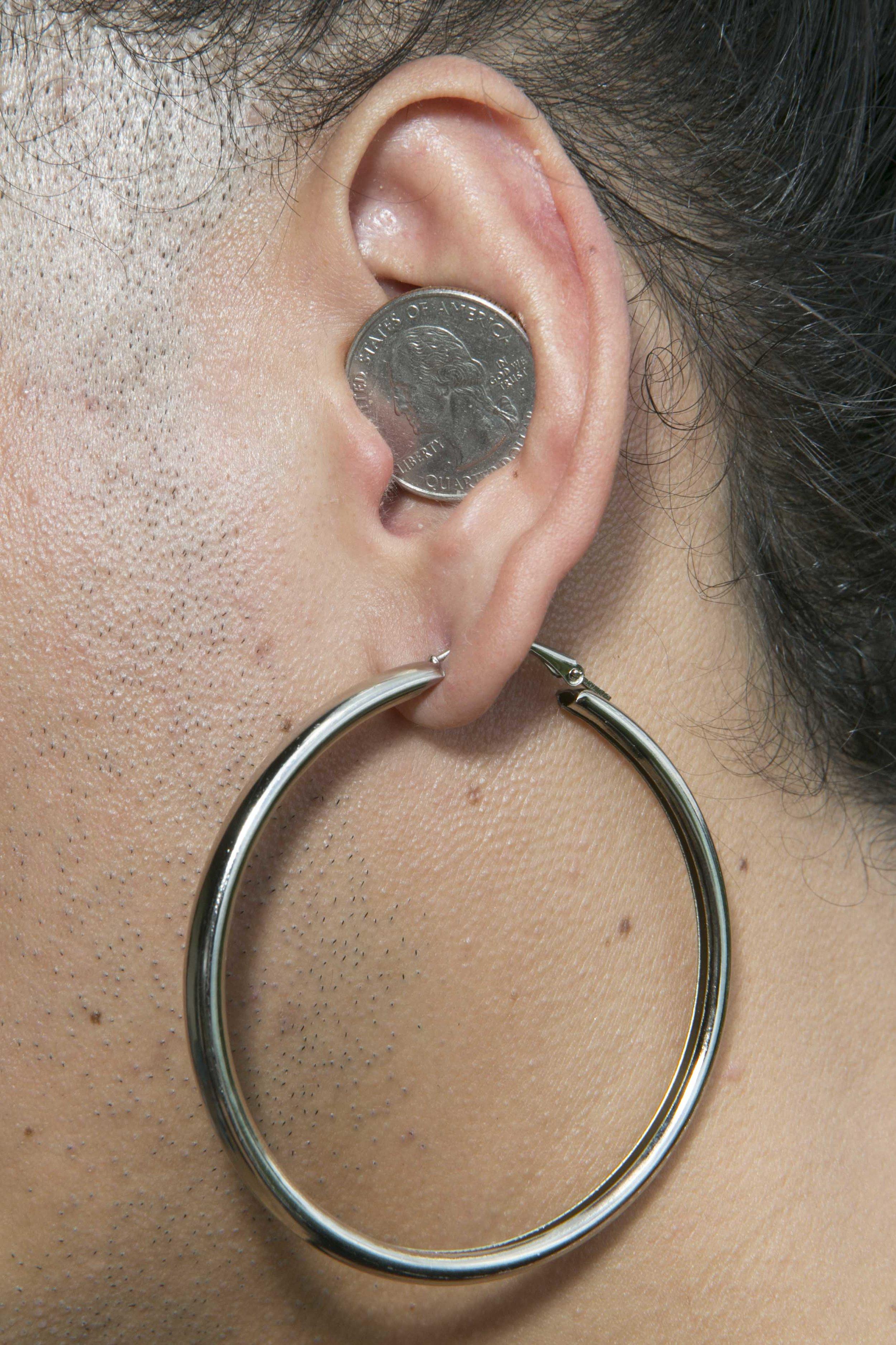 NadiA espera el bus con una cora ($0.25) que robó de la cartera de su padre. Andar monedas en la oreja es considerado algo muy masculino en este país y, como ella fue criada como hombre, mantiene algunos de estos hábitos. Antes de la dolarización en El Salvador, solían poner colones en sus orejas.