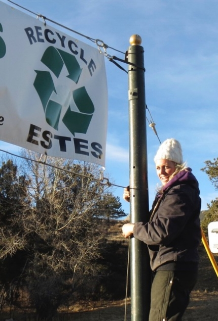 A townemployee finishes raisingthe Estes Park's28-foot recycling banner for the first time. (CRC photo)