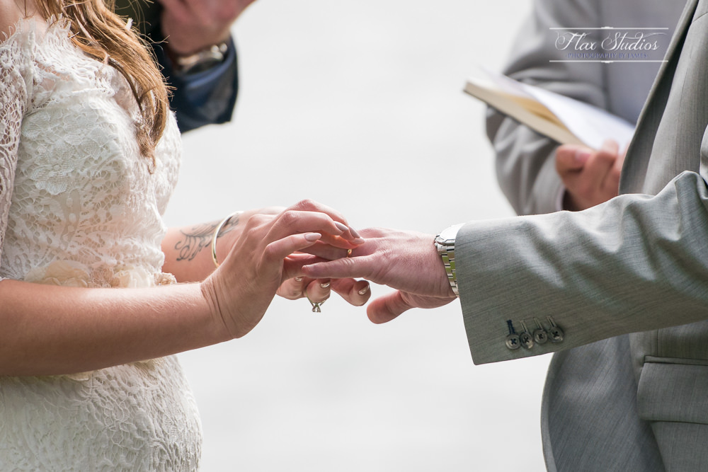 Close up of bride putting the wedding ring on the groom